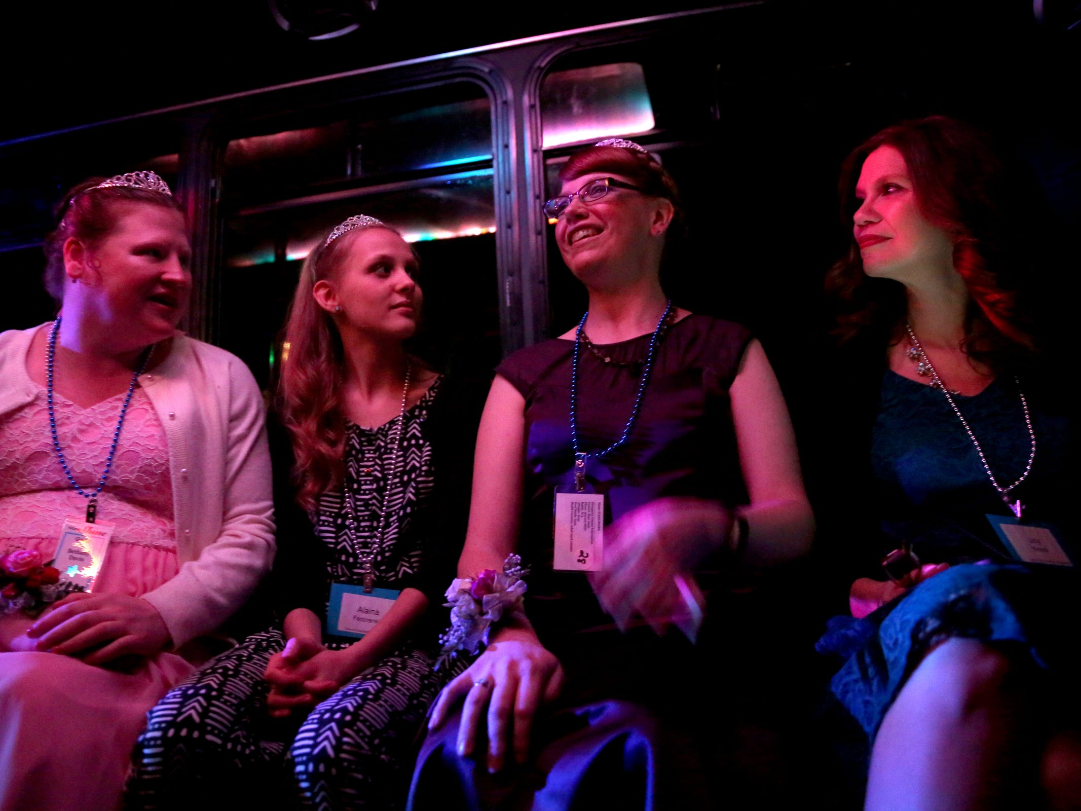 Kris Burden, second from right, 36, of Salem, and other ride in a party bus at Night to Shine, a prom night experience for people with special needs, at Salem Alliance Church on Friday, Feb. 8, 2019.