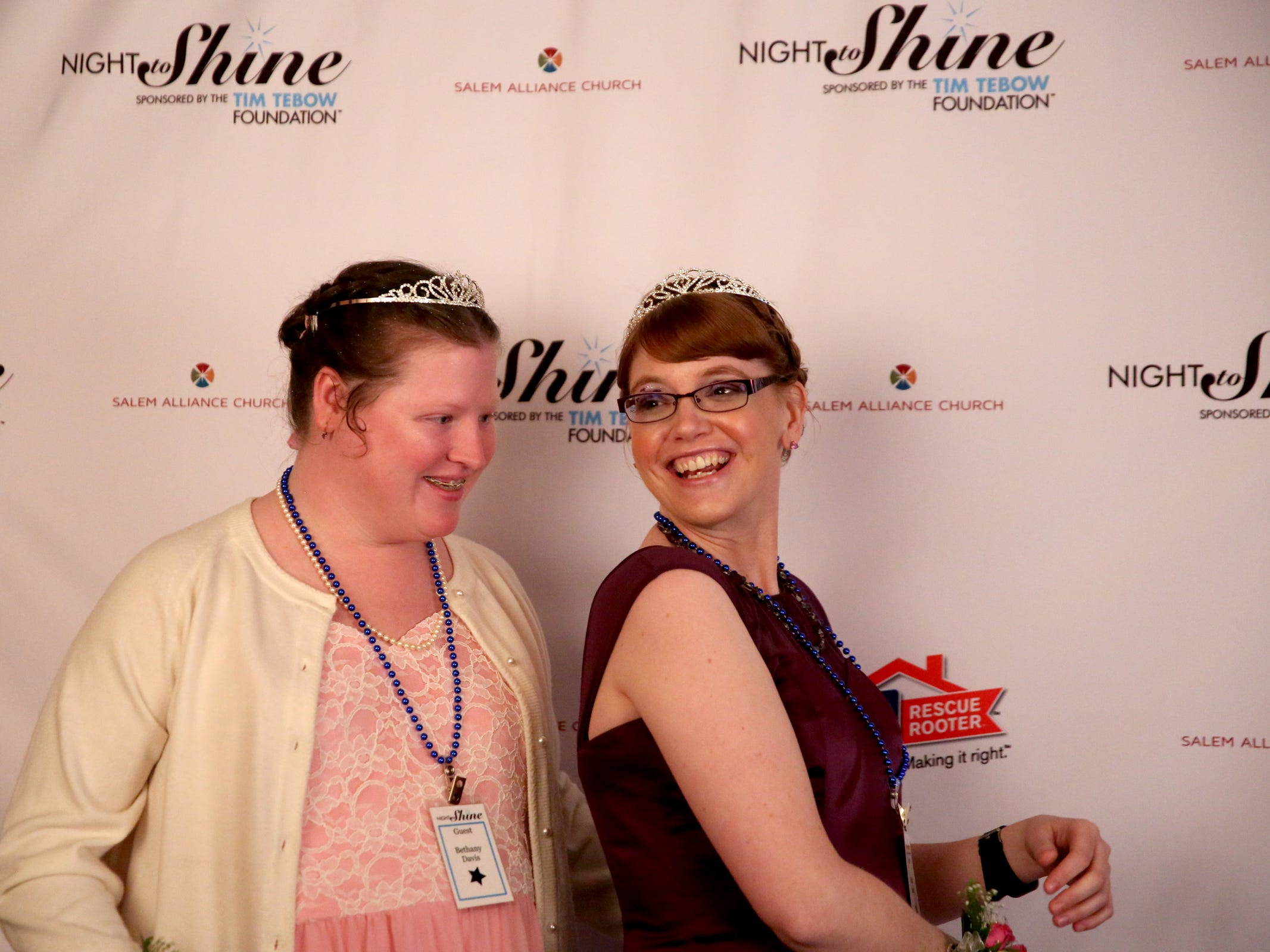 Kris Burden, right, 36, of Salem, and her friend Bethany Davis, 34, of Alliance, have their photos taken at Night to Shine, a prom night experience for people with special needs, at Salem Alliance Church on Friday, Feb. 8, 2019.