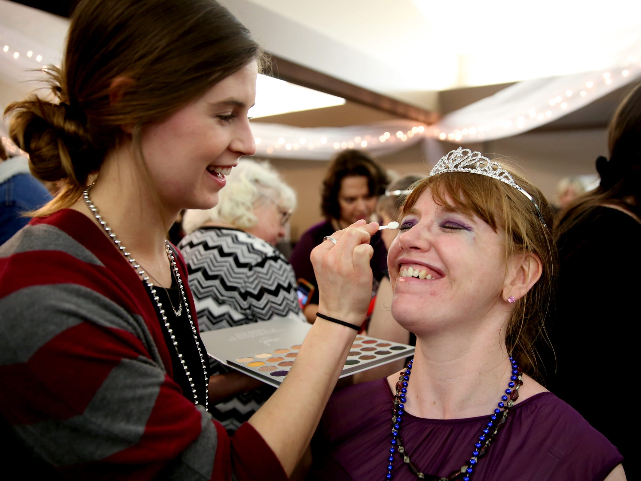 Kris Burden, 36, of Salem, has her makeup done by volunteer Sabrina Lozier at Night to Shine, a prom night experience for people with special needs, at Salem Alliance Church on Friday, Feb. 8, 2019.