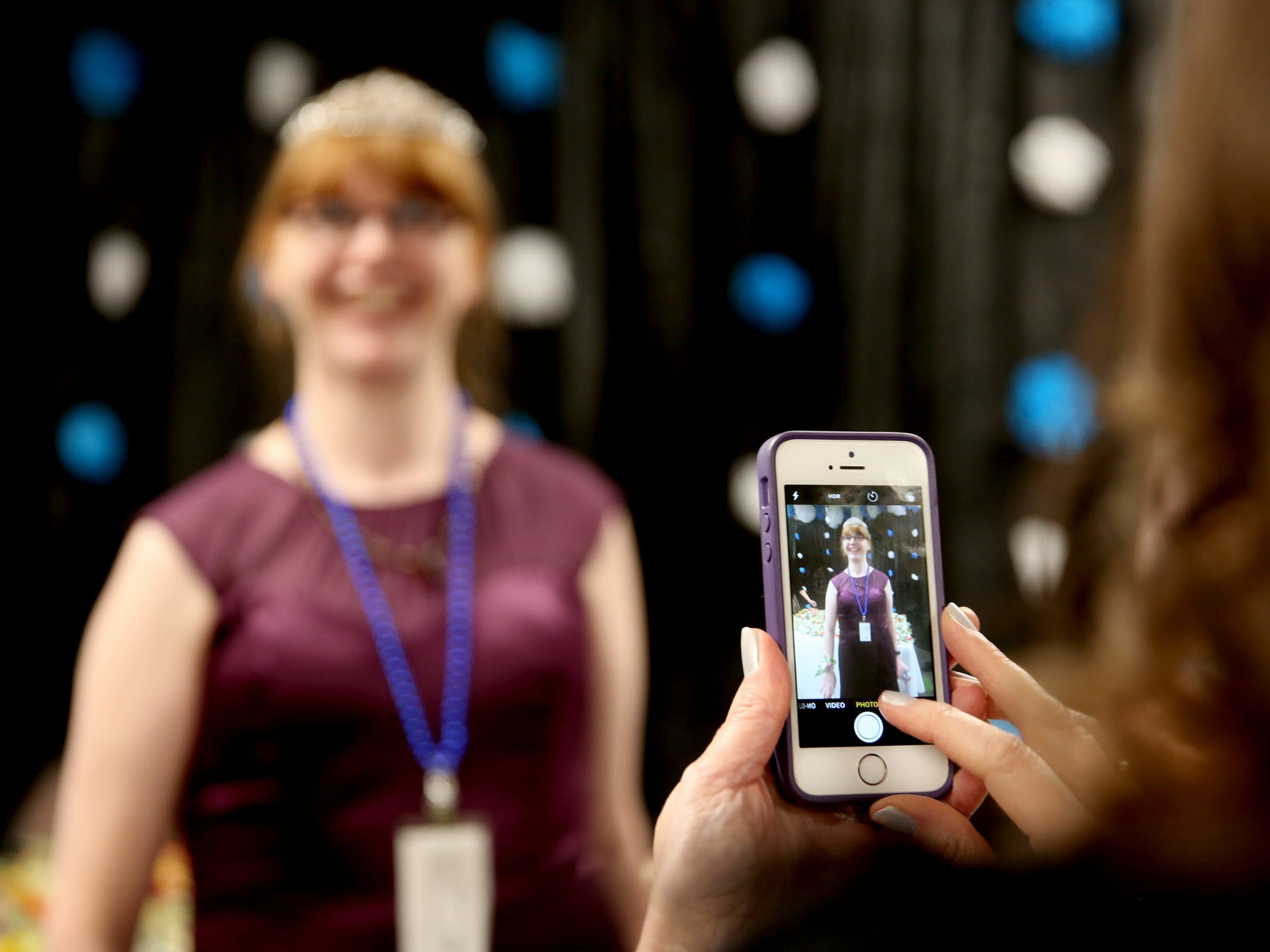 Volunteer Joy Biondi, of Keizer, takes a photo of her designated partner, Kris Burden, of Salem, during Night to Shine, a prom night experience for people with special needs, at Salem Alliance Church on Friday, Feb. 8, 2019.
