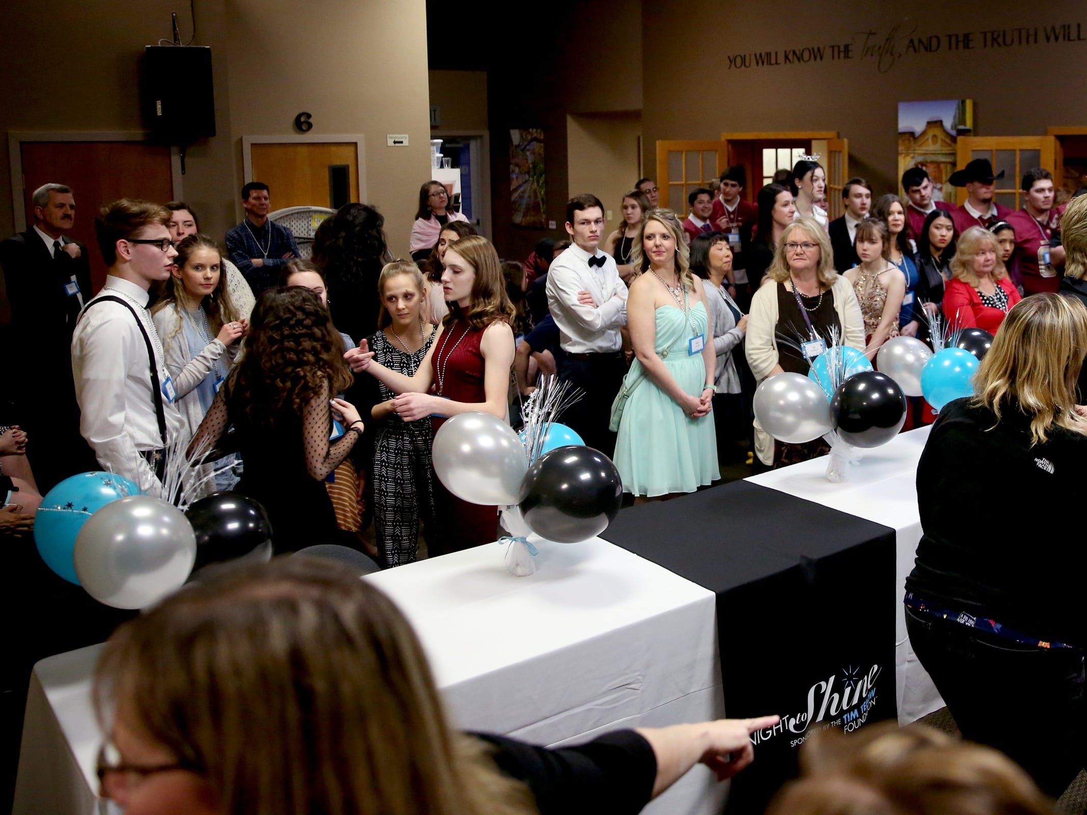 Volunteers wait to be paired up with their dance partners during Night to Shine, a prom night experience for people with special needs, at Salem Alliance Church on Friday, Feb. 8, 2019.