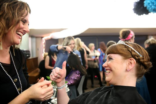 Kris Burden, 36, of Salem, give a thumbs up after her hair was done by volunteer Janna Reece at Night to Shine, a prom night experience for people with special needs, at Salem Alliance Church on Friday, Feb. 8, 2019.