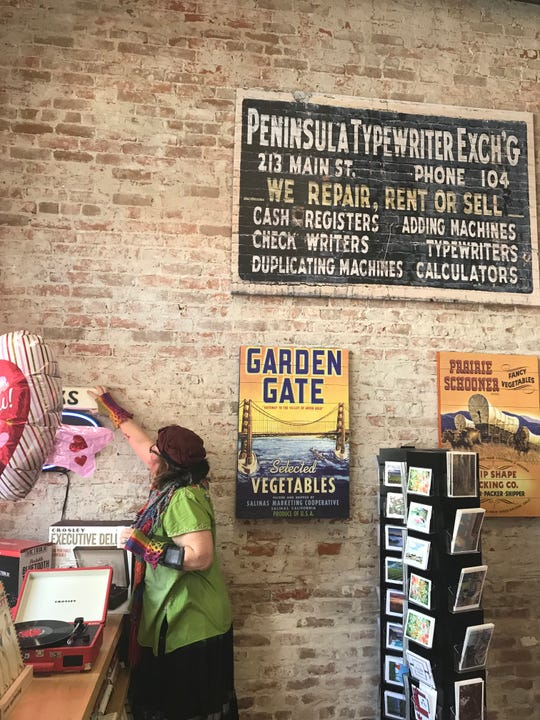 A sign for the Peninsula Typewriter Exchange hangs inside the bookstore; it was found when the building owner took down a neon sign hanging in the back.
