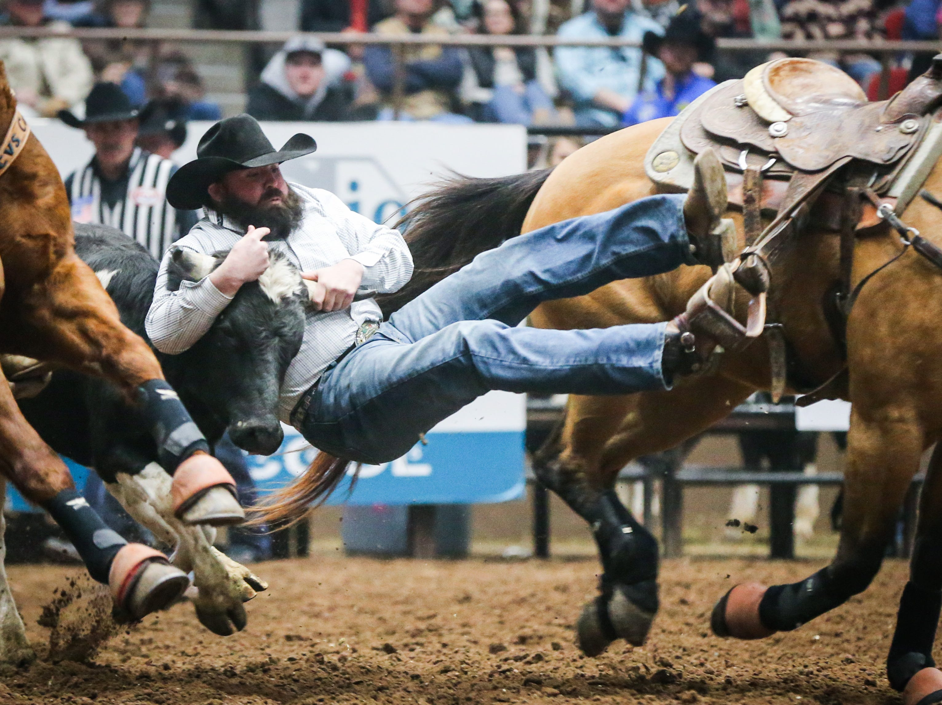 Cody Dollery rides out to wrestle a steer during the San Angelo Stock Show & Rodeo matinee show Saturday, Feb. 9, 2019, at Foster Communications Coliseum.