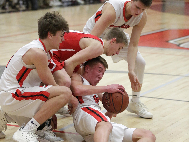 Oostburg's Braden Dirkse, center, grips the ball tightly against Manitowoc Lutheran, 2019, in Oostburg, Wis. Gary C. Klein/USA TODAY NETWORK-Wisconsin