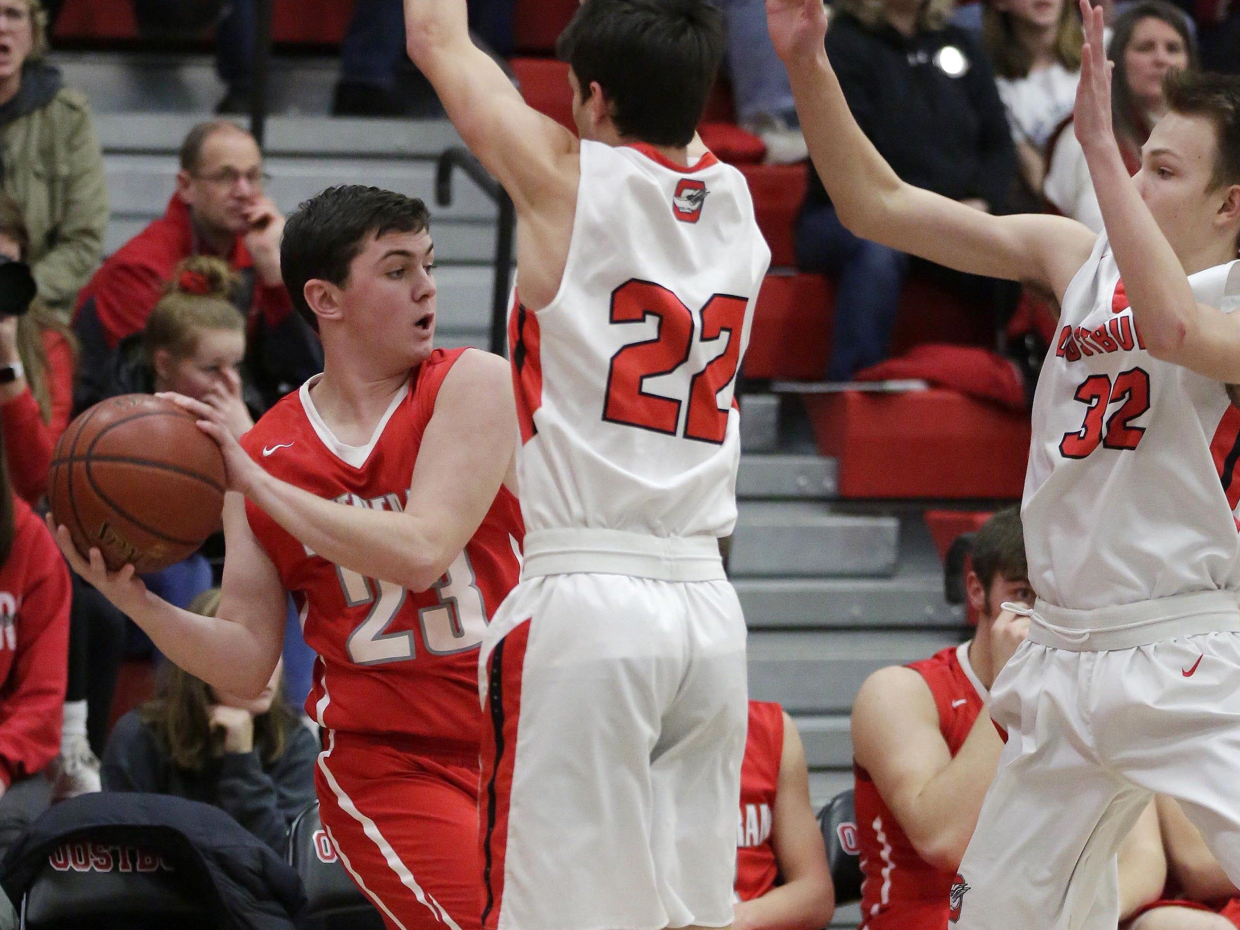 Manitowoc Lutheran's Josh Diel (23) looks to pass the ball beyond Oostburg's Brady Wisse (23) and Josh Meerdink (32), Friday, February 8, 2019, in Oostburg, Wis. Gary C. Klein/USA TODAY NETWORK-Wisconsin