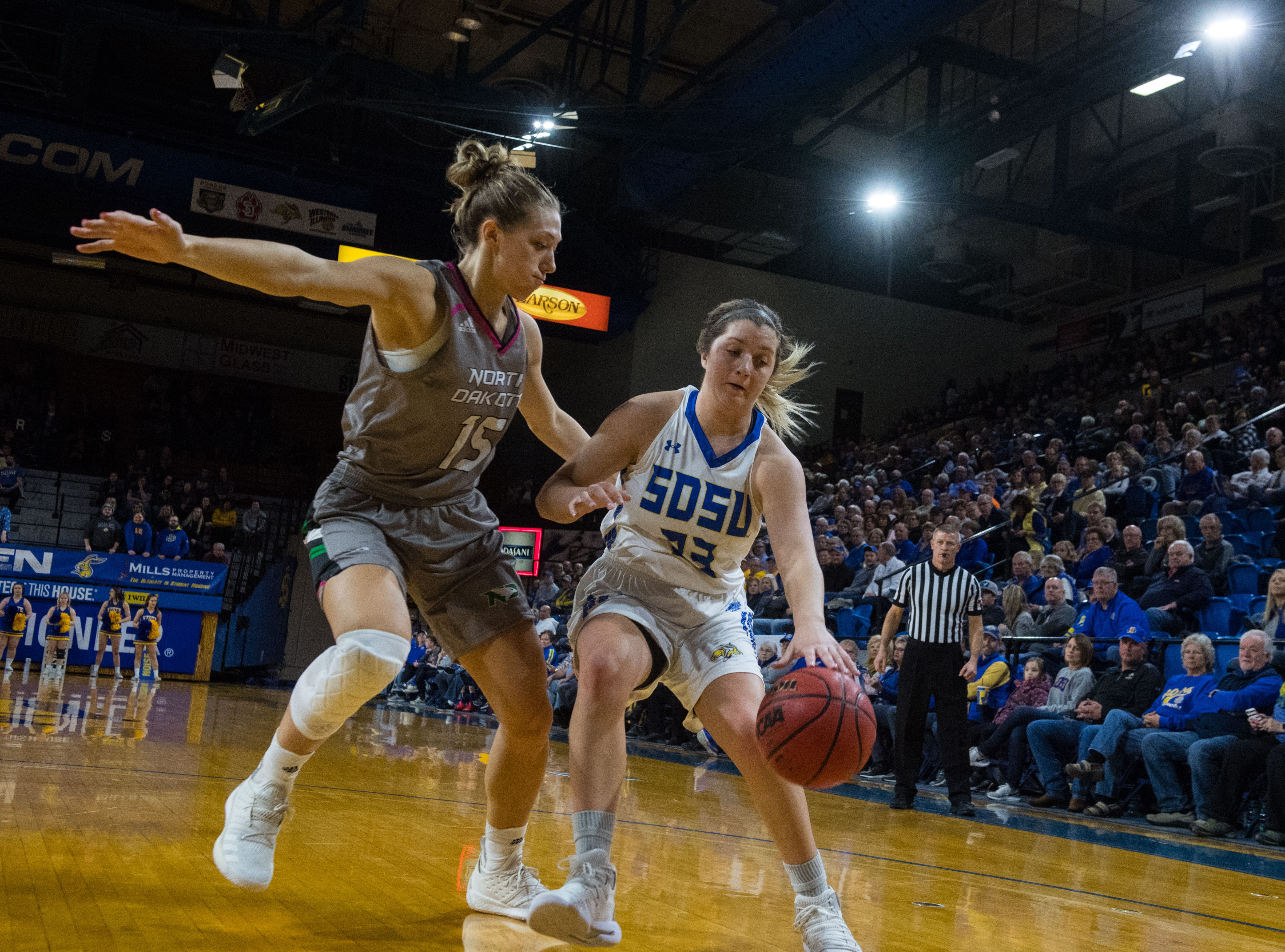 South Dakota State's Paiton Burckhard dribbles the ball past North Dakota player during a game in Brookings, S.D., Saturday, Feb. 9, 2019.