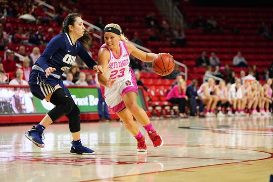 South Dakota guard Madison McKeever tries to dribble around an Oral Roberts defender during their game on Saturday, Feb. 9, 2019.