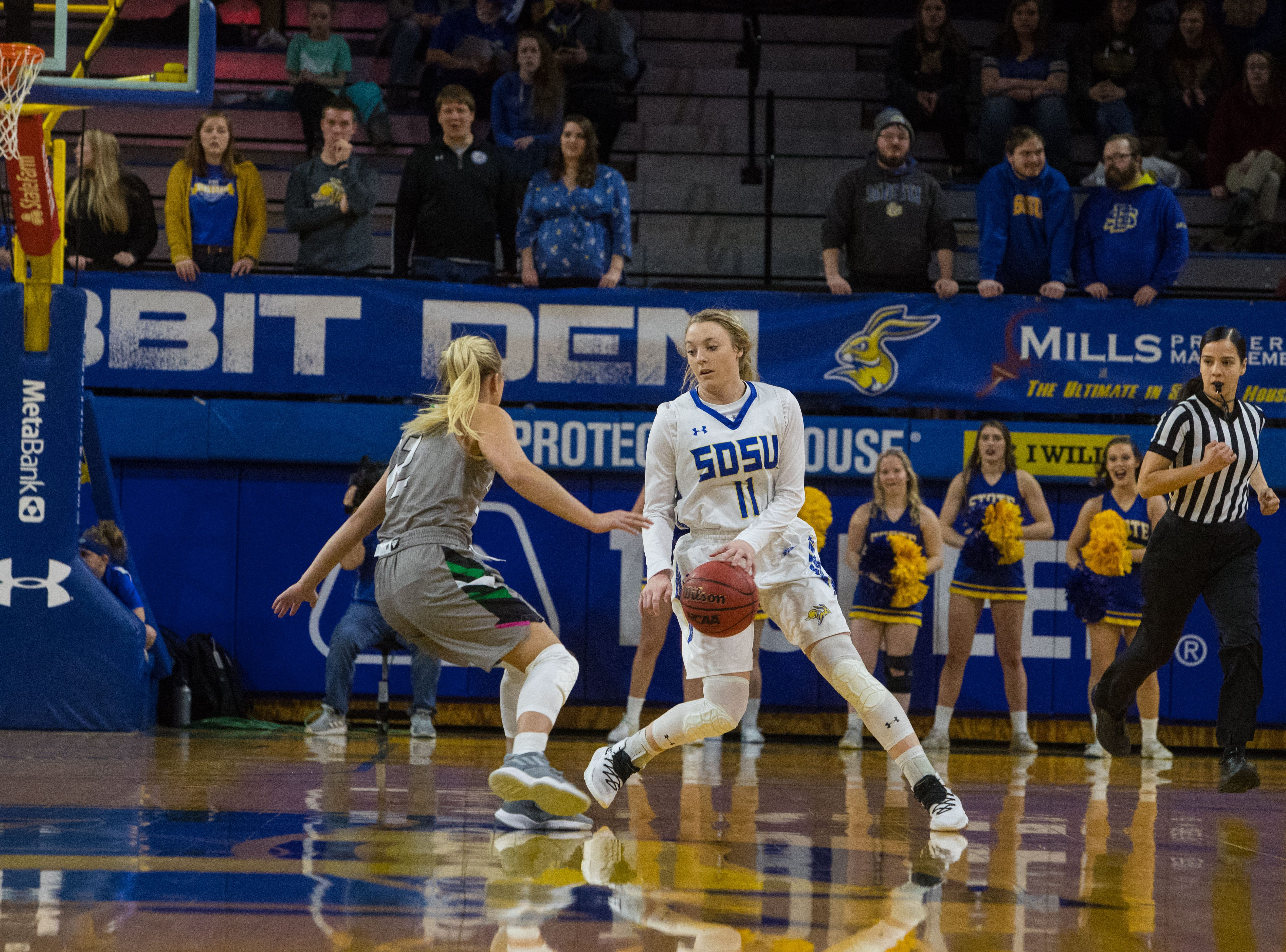 South Dakota State's Madison Guebert (11) dribbles the ball past North Dakota player during a game in Brookings, S.D., Saturday, Feb. 9, 2019.