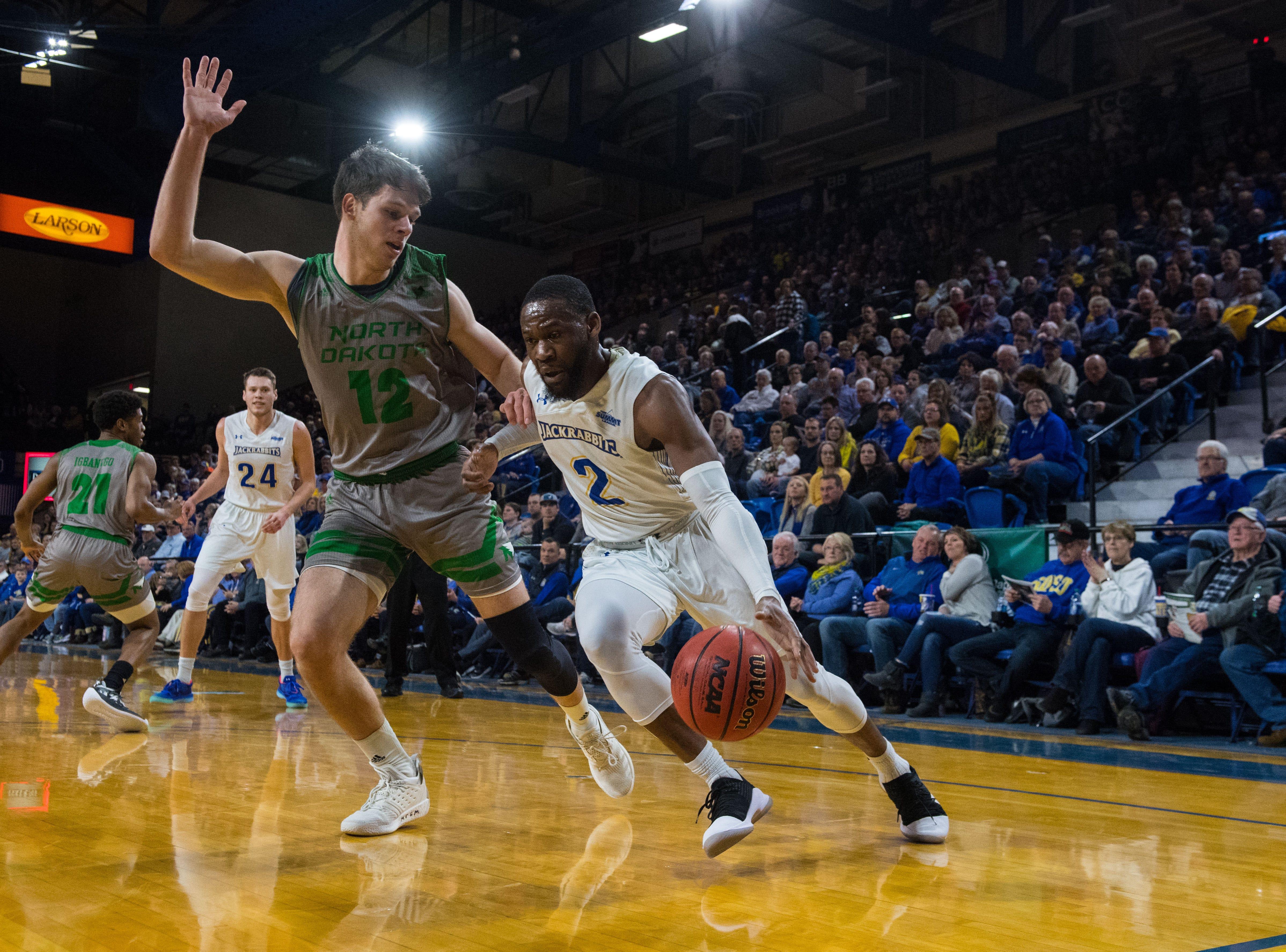 South Dakota State's Tevin King (2) dribbles the ball past North Dakota's Filip Rebraca (12) during a game in Brookings, S.D., Saturday, Feb. 9, 2019.