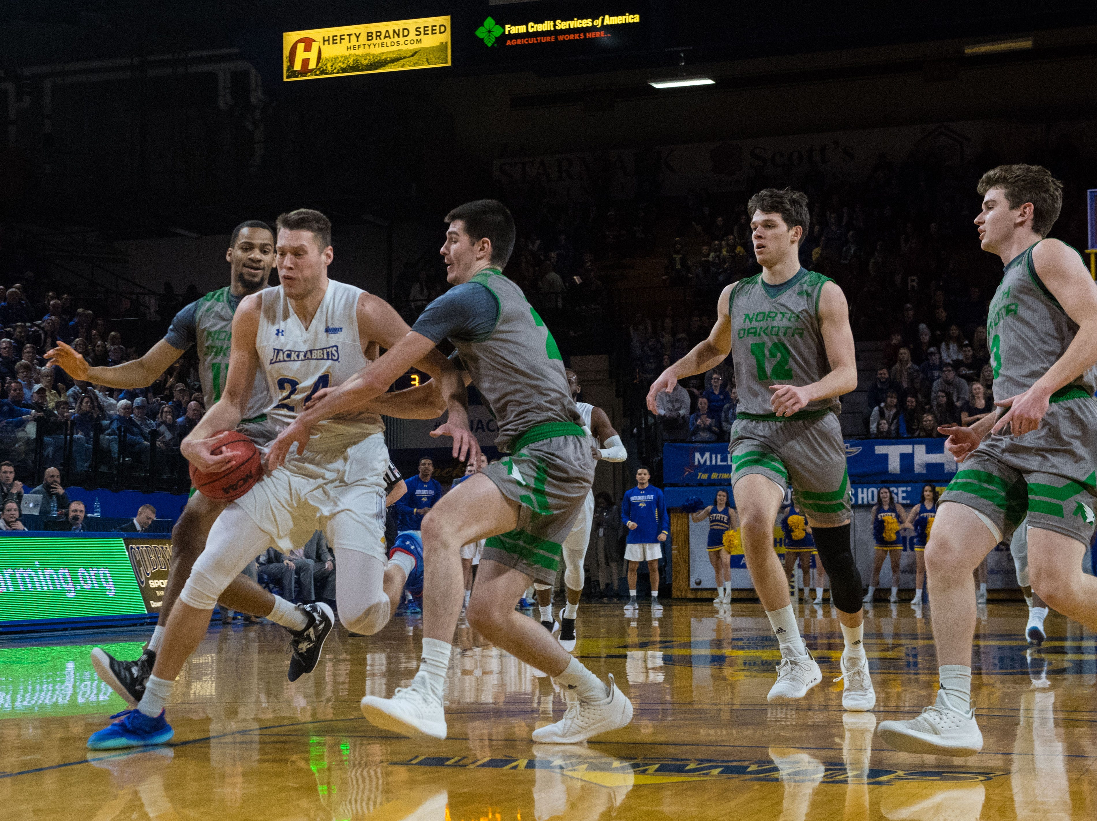South Dakota State's Mike Daum (24) dribbles the ball past North Dakota players during a game in Brookings, S.D., Saturday, Feb. 9, 2019.