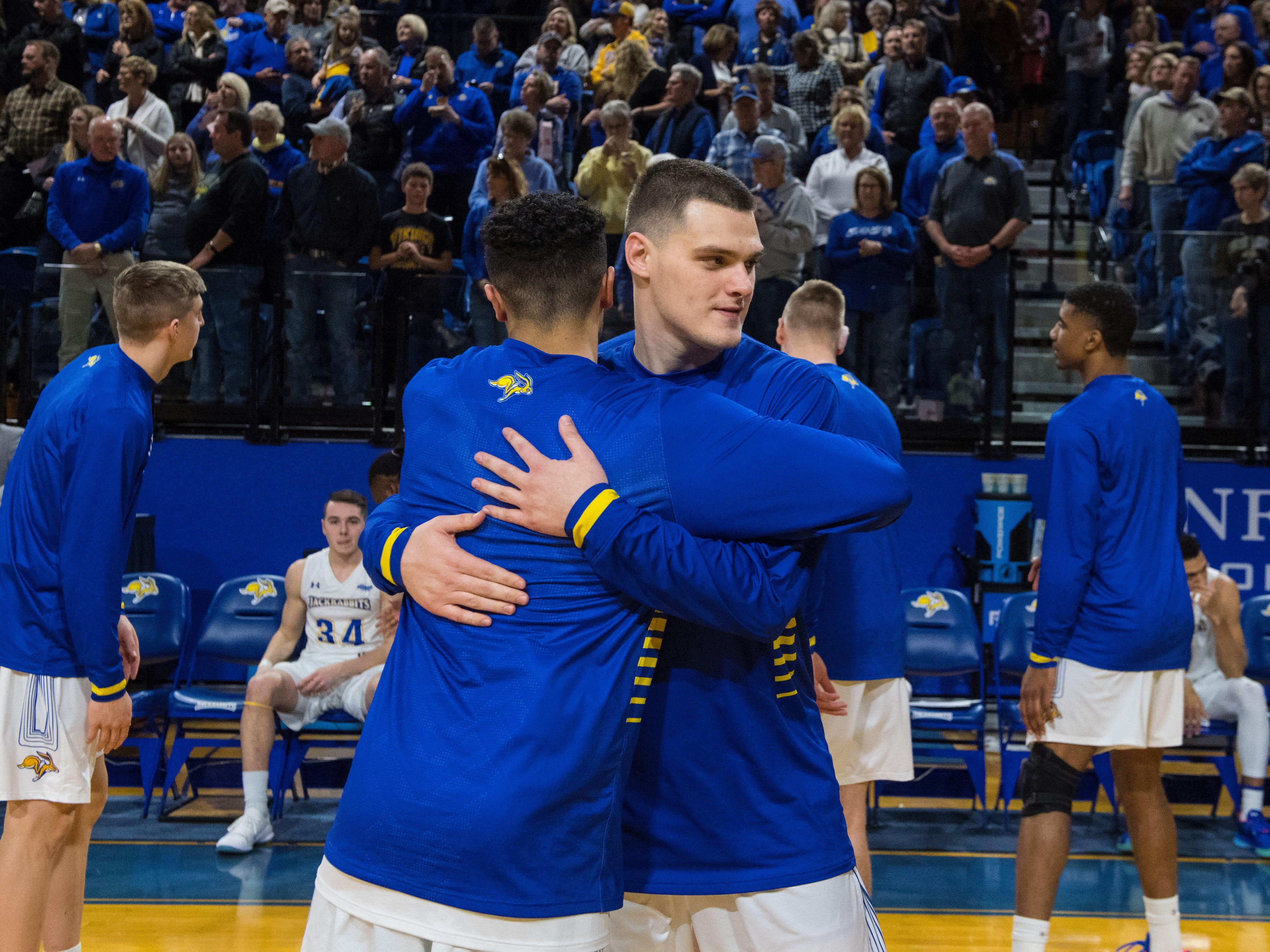 South Dakota State players hug before the game against North Dakota in Brookings, S.D., Saturday, Feb. 9, 2019.