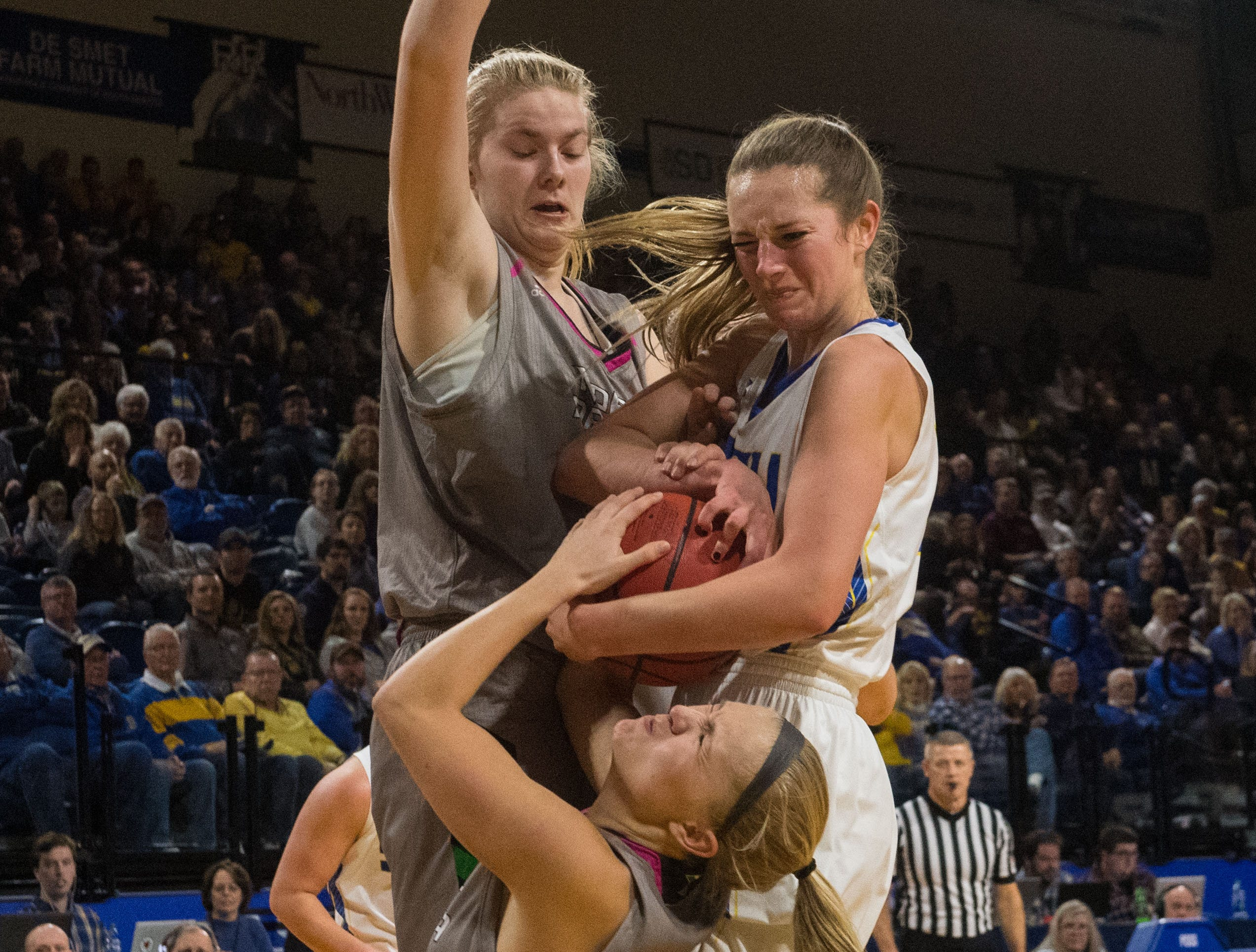 South Dakota State's Tagyn Larson (24) and North Dakota players grab for the ball during a game in Brookings, S.D., Saturday, Feb. 9, 2019.