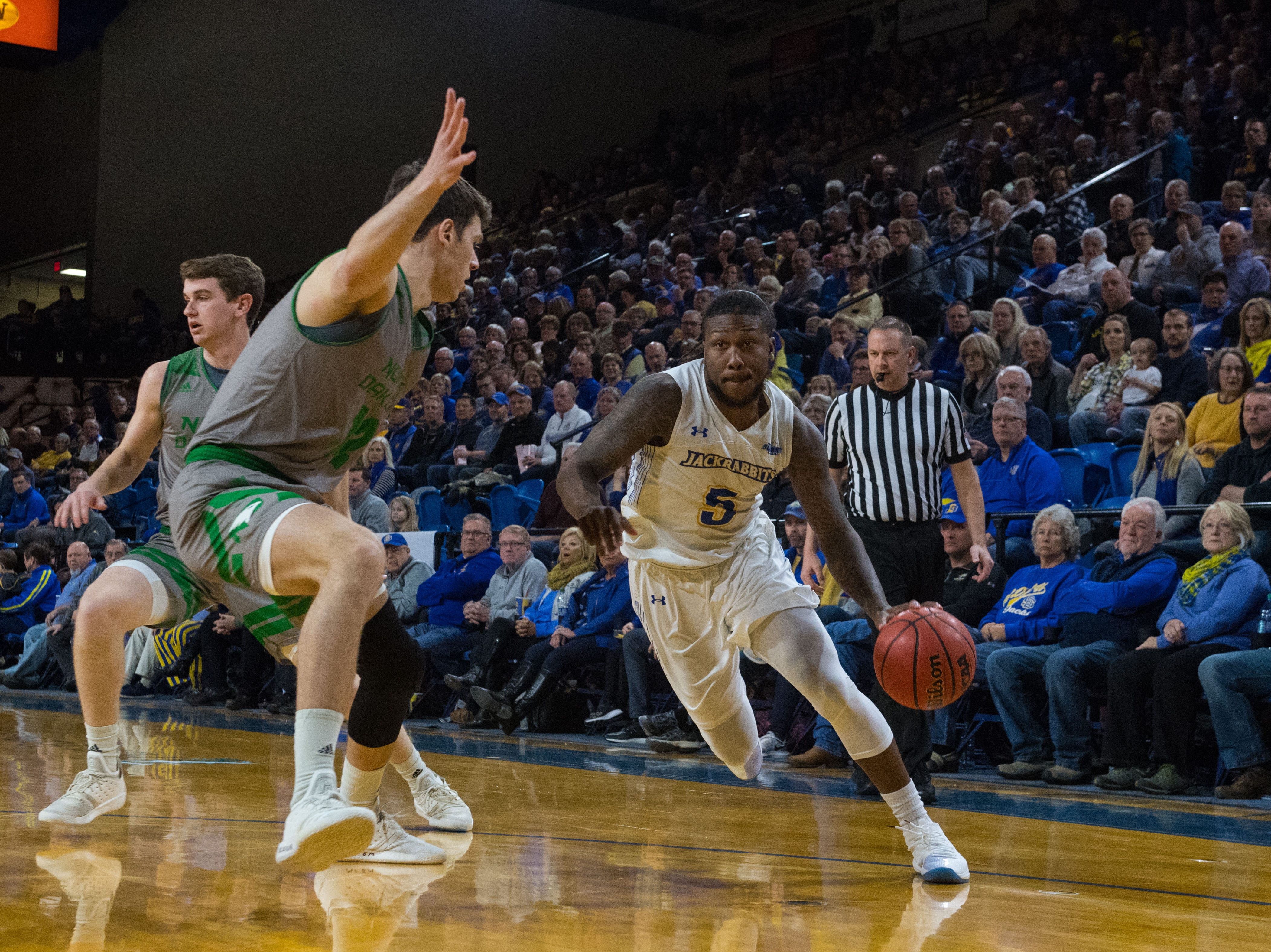 South Dakota State's David Jenkins (5) dribbles the ball past North Dakota player during a game in Brookings, S.D., Saturday, Feb. 9, 2019.