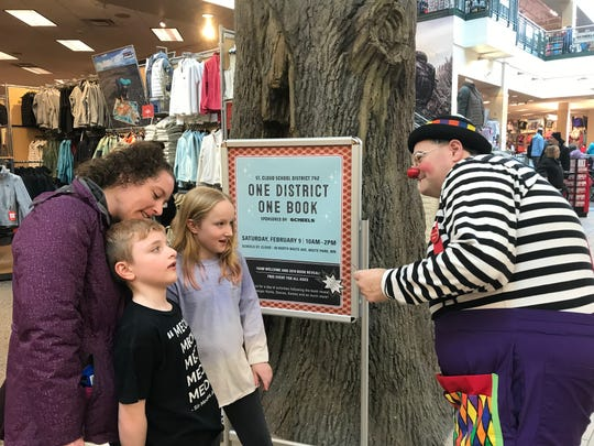 Baloo Baphoon hands out magic tricks to Ariana Outhwaite, 10,  and Beckett Outhwaite, 6, with their mother Jessica Outhwaite at Scheels Saturday, Feb. 9, as part of St. Cloud Area School District's lauch of its 2019 One District One Book program.
