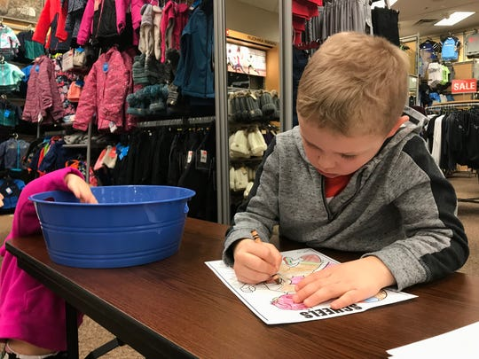 Easton Barrett, 5, colors at Scheels on Saturday, Feb. 9. The color station was one of many activities tied to the One District One Book lauch event for St. Cloud Area School District.
