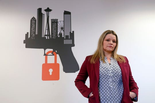 In this Thursday, Feb. 7, 2019 photo, Kimberly Wyatt, a King County senior deputy prosecutor who is part of a regional unit that enforces Extreme Risk Protection Orders (ERPO), poses for a portrait near the logo for the unit in Seattle. Since last year's mass shooting at a Florida high school, states have seen a surge of interest in laws intended to make it easier to disarm people who show signs of being violent or suicidal. Washington voters approved such a law overwhelmingly in 2016. (AP Photo/Elaine Thompson)