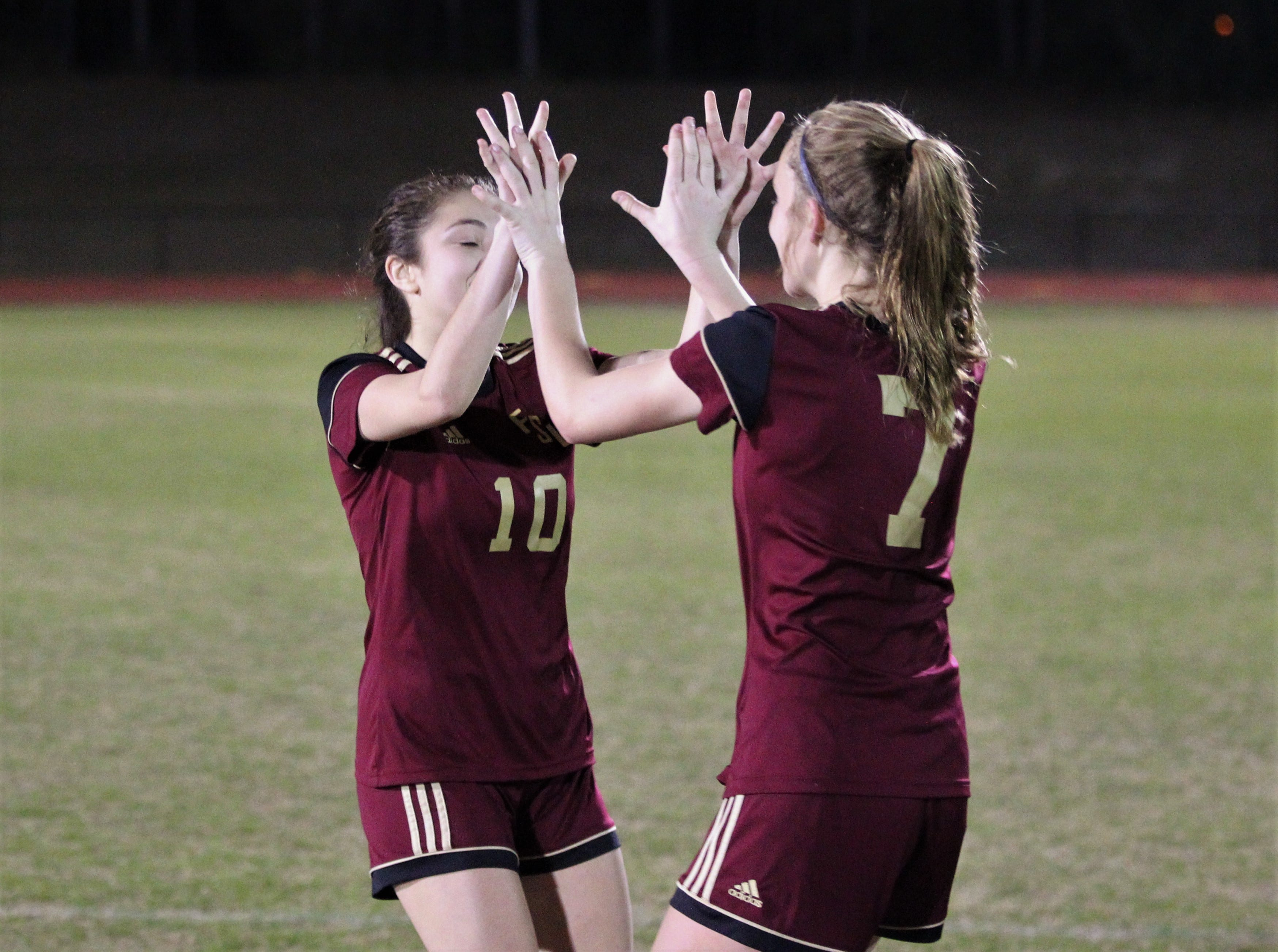 Florida High's Adriana Limburg is high-fived by Ava Dubois after making a PK as South Walton's girls soccer team edged the Seminoles 5-4 in a penalty-kick shootout during a Region 1-2A semifinal on Feb. 8, 2019.