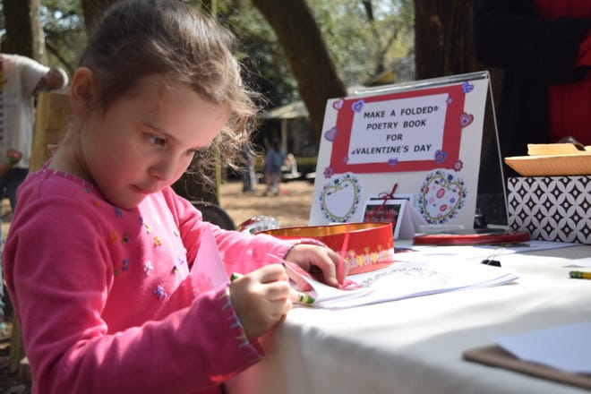Lily Tupper, 5, draws in a folded poetry book Saturday during the Matinee of the Arts at the Tallahassee Museum.