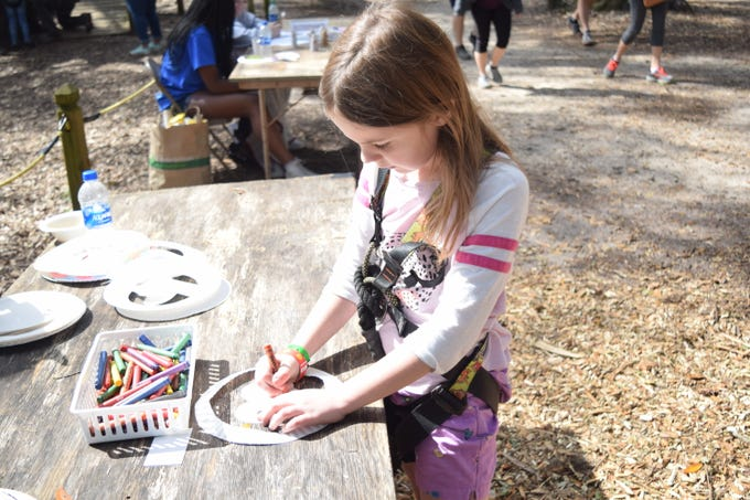 Thia Gunn, 8, draws a flamingo on her paper crown Saturday during the Matinee of the Arts at the Tallahassee Museum. Her favorite part of the day was going down the zip line.