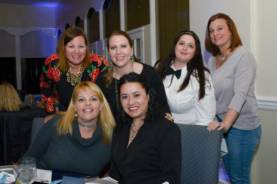 Jennifer Brown, standing, left, Jennifer Wiggins, Angela Connolly and Kim Phillips, with  Christine Iannotti, seated, and Luv Lima at Family Meals' Black Tie, Blue Jeans & Bingo fundraiser in Fort Pierce.