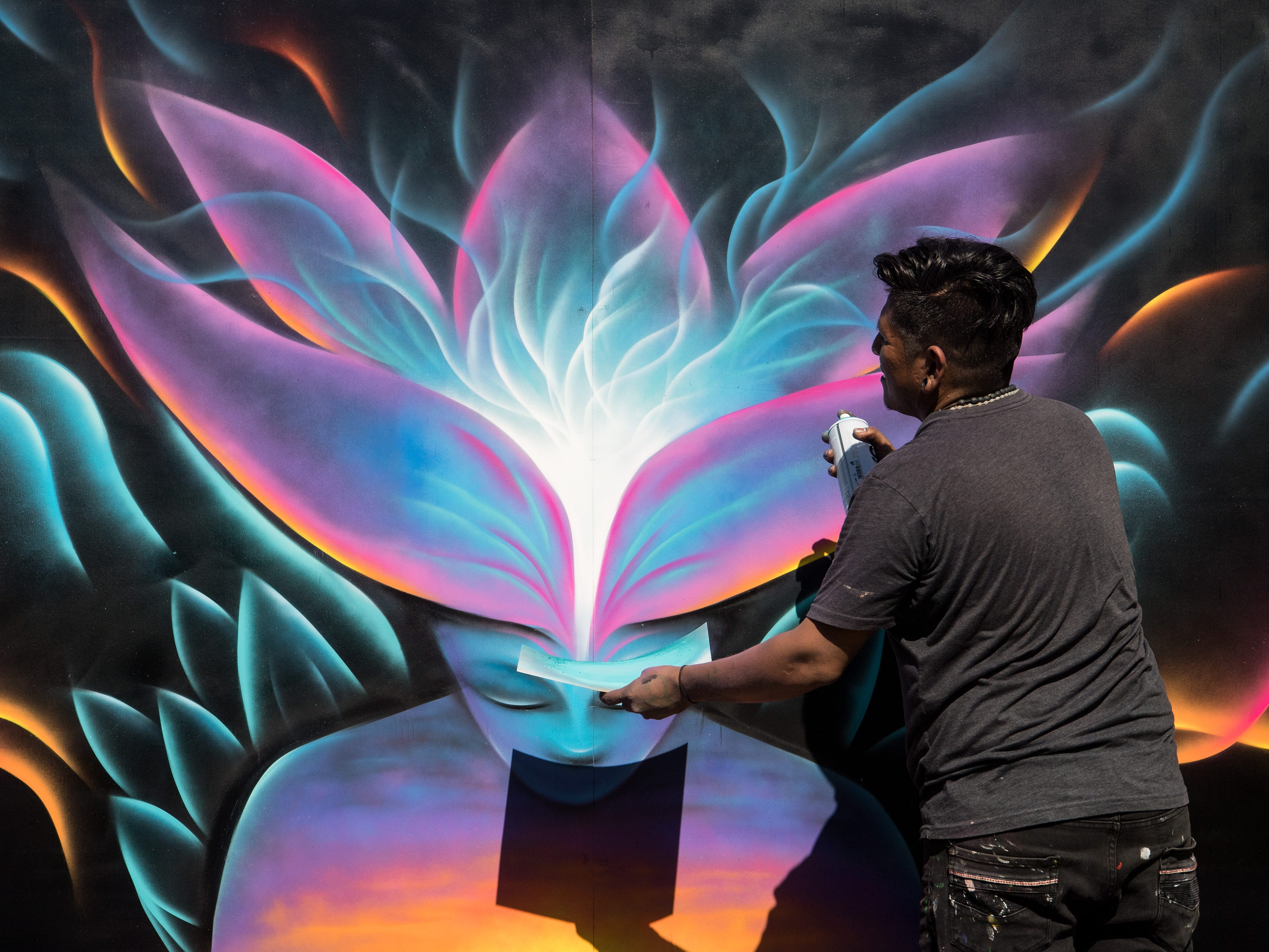 "Marcos Conde, an artist from Fort Lauderdale, uses spray paint for his mural as part of the Off the Wall Urban Art Competition debut at ArtsFest 2019 on Saturday, Feb. 9, 2019, at Memorial Park in downtown Stuart. ""Well, we're focusing on the theme of world cultural unity,"" he said, referring to the theme of ""unity, diversity and the spirit of world culture"" required for the competition. ""So, the sunset is like a representation of unity, and the boat (not pictured) is like the world — the boat we're all in,"" he added. The Arts Council of Martin County's signature event, with an overall theme of ""Succumb to Your Senses,"" continues from 10 a.m. to 5 p.m. on Sunday."