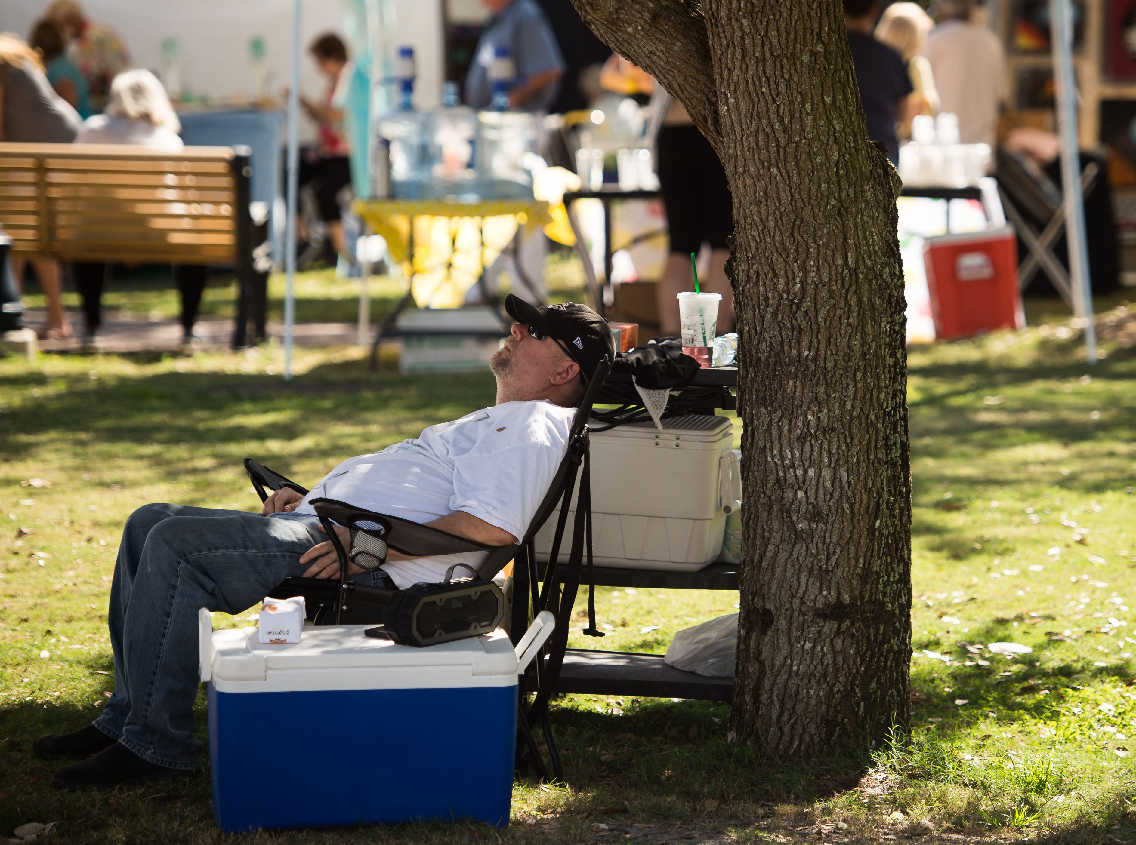 "A Martin County High School art teacher on a break, identified by his colleagues as Bryan Johnson, naps in the shade near the school's booth at The Arts Council of Martin County's ArtsFest 2019, themed ""Succumb to Your Senses,"" on Saturday, Feb. 9, 2019, at Memorial Park in downtown Stuart."