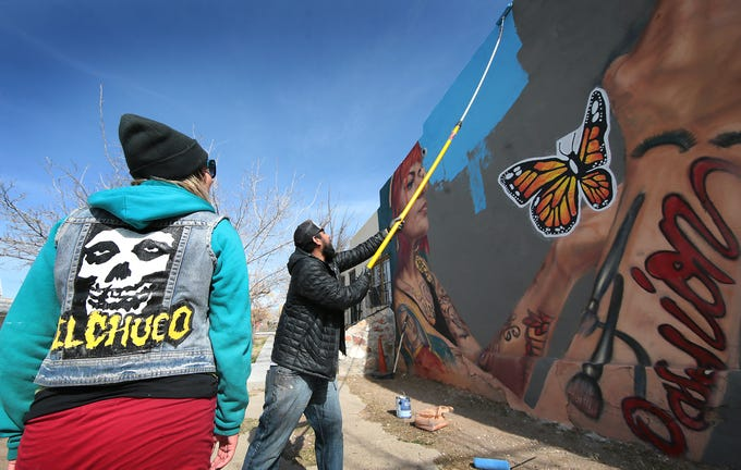 """El Paso muralist Jesus """"Cimi"""" Alvarado on Saturday works to finish his latest mural at the corner of Tays Street and Delta Drive in the Segundo Barrio. The project is meant to emphasize the border's unity and safety ahead of President Donald Trump's visit Monday to El Paso."""