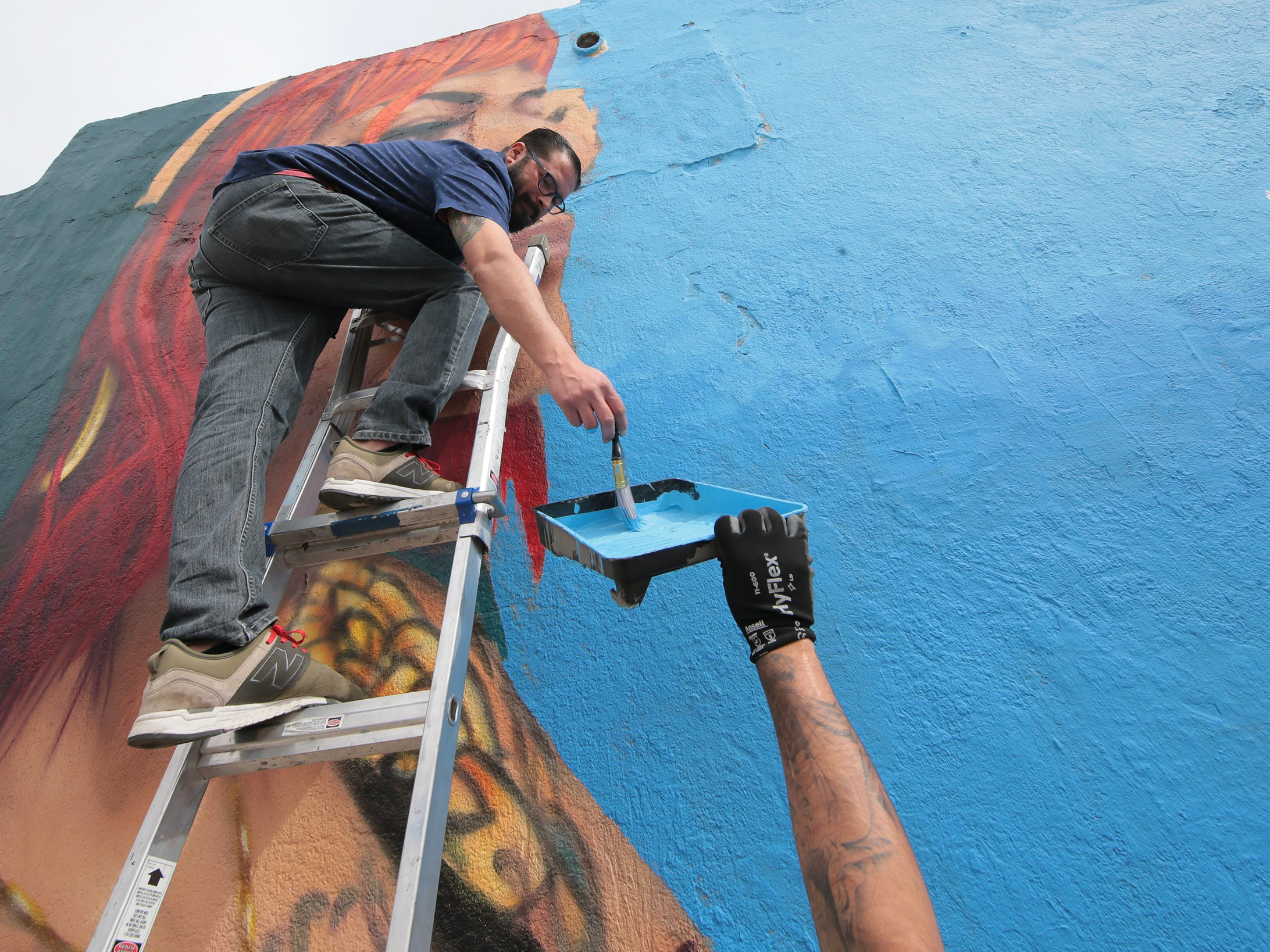"""El Paso muralist Cimi Alvarado is working to finish his latest mural at the corner of Tays and Delta in the Segundo Barrio. The mural follows closely a poem by Pavel Freidman, a child who was murdered at the Theresienstadt Concentration Camp. Alvarado said we can't repeat this history, citing the child migrant detention centers where refugees were being held.  The mural is a collaboration between Cimi Alvarado, The University of St. Thomas' VISION Program, Kalavera Culture Shop, Gloria Yrrobali and Martin """"Blast"""" Zubia."""