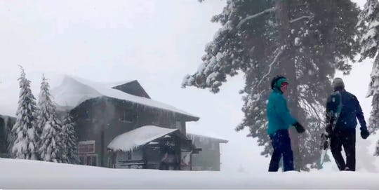This Tuesday photo from video by Joel Keeler shows people approaching the showed-in Montecito Sequoia Lodge in Kings Canyon National Park in California's Sierra Nevada.