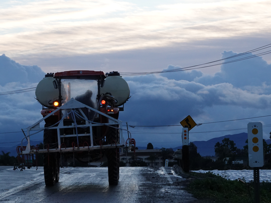 A man drives a farm vehicle past hoop houses, at right, in Camarillo early Saturday as clouds hang in the distance.