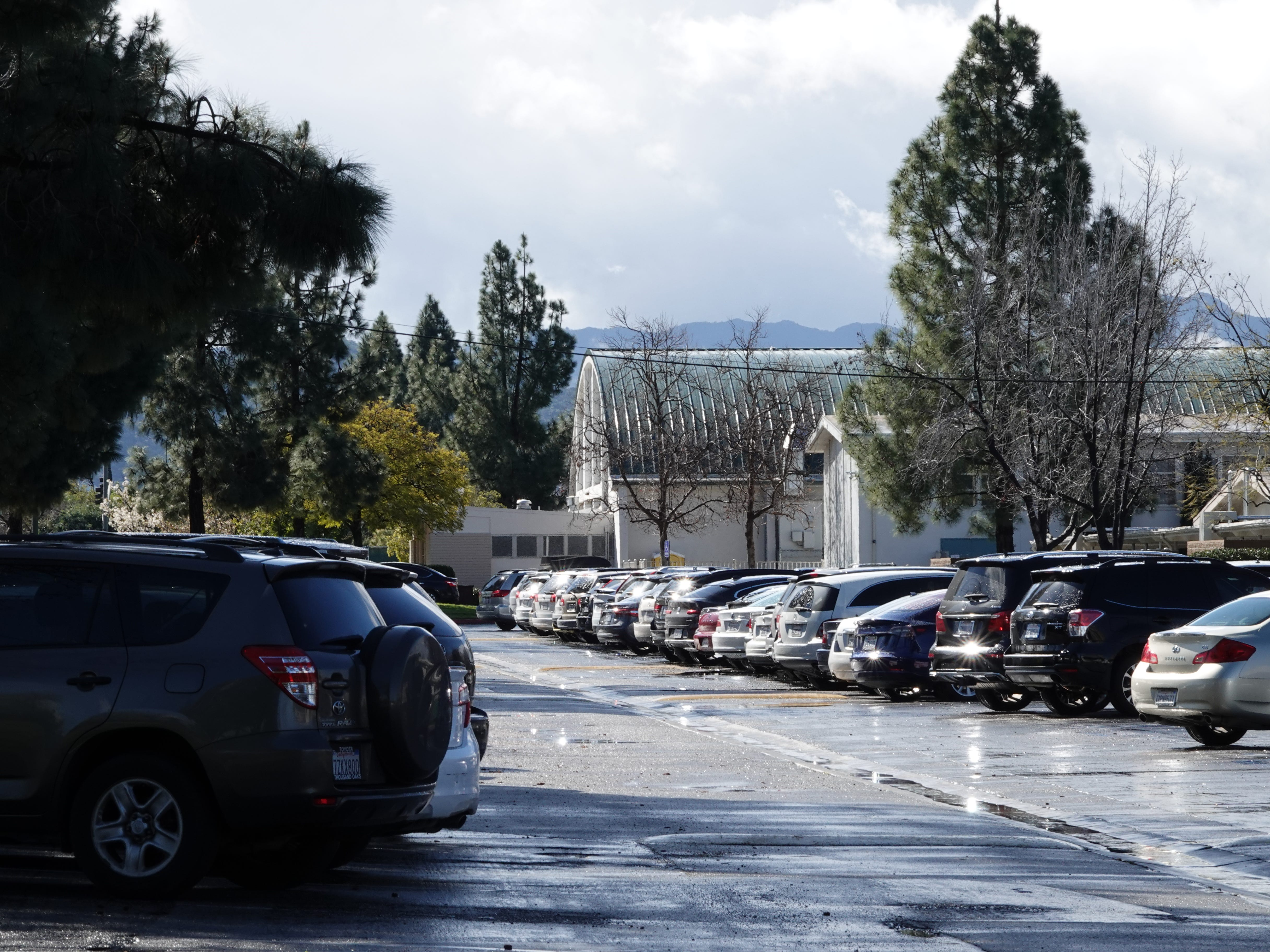 A parking lot at Thousand Oaks High School is shown with the rounded roof of the gymnasium at rear Saturday morning. A woman suffered life-threatening injuries Friday night when a student allegedly ran over her intentionally outside the gym, authorities say.
