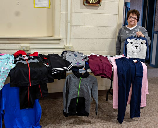 Pam McNamee of the Millville Woman's Club and chairperson for the club's project to benefit Court Appointed Special Advocates, displays some of the sweat pants and shirts that were collected. These items will be donated to foster children in the CASA program for Cumberland, Gloucester and Salem counties. McNamee also serves as CASA Southern District chairperson for the New Jersey State Federation of Women's Clubs.