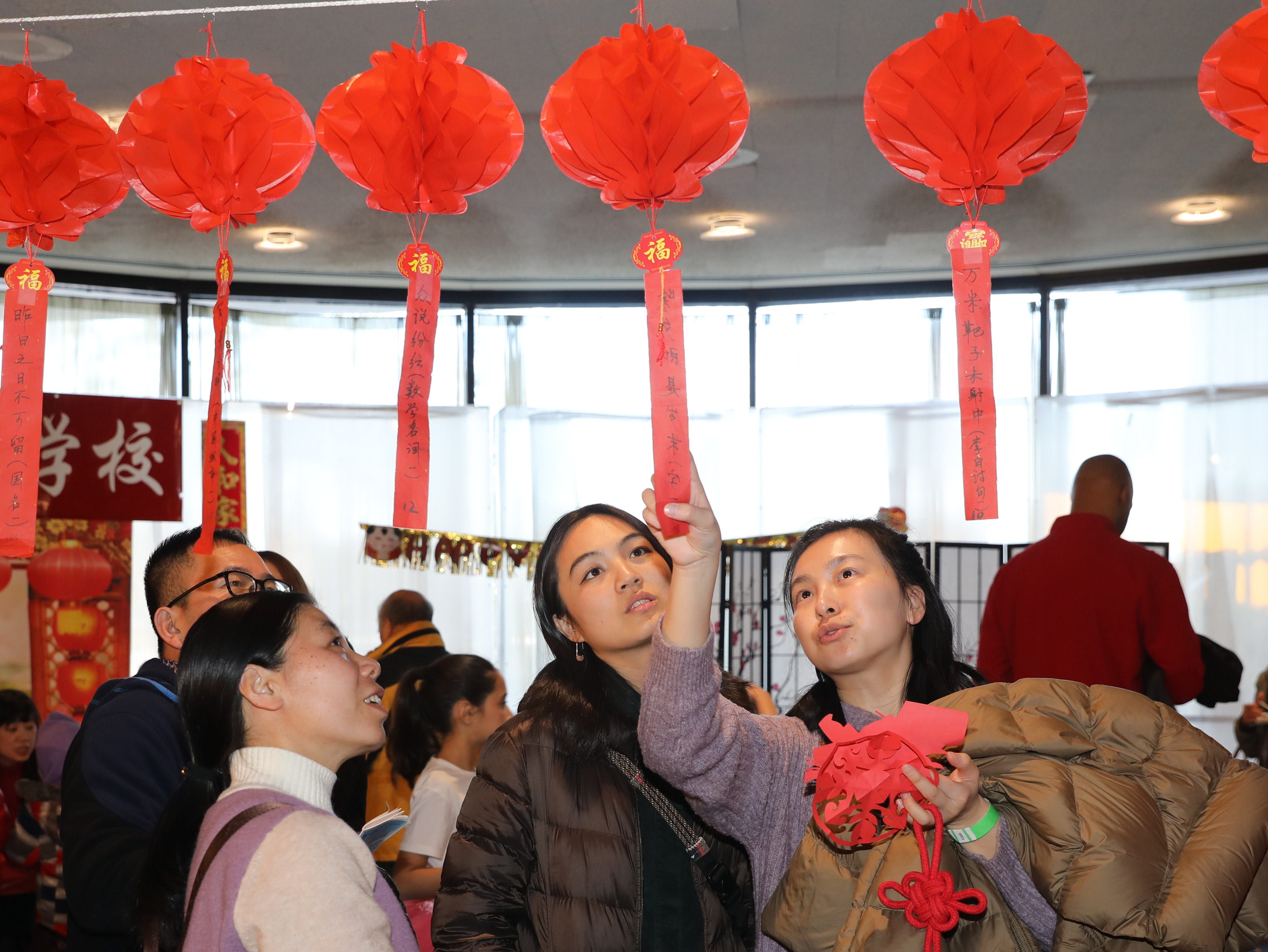 Leila Yu, center and Yang Guo, right, look at some puzzles hanging from lanterns, during the 30th Chinese New Year Festival, the Year of the Pig, sponsored by WACA (Westchester Association of Chinese Americans), at The Performing Arts Center at Purchase College SUNY, Feb. 9, 2019.