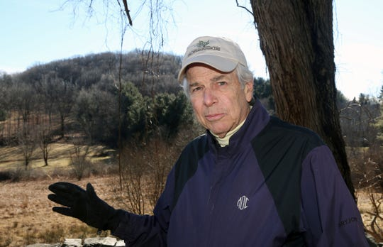 John Stockbridge talks about the proposed cell tower that was supposed to go on the hill behind him that boarders the Marsh Sanctuary in Mount Kisco Feb. 8,  2019.