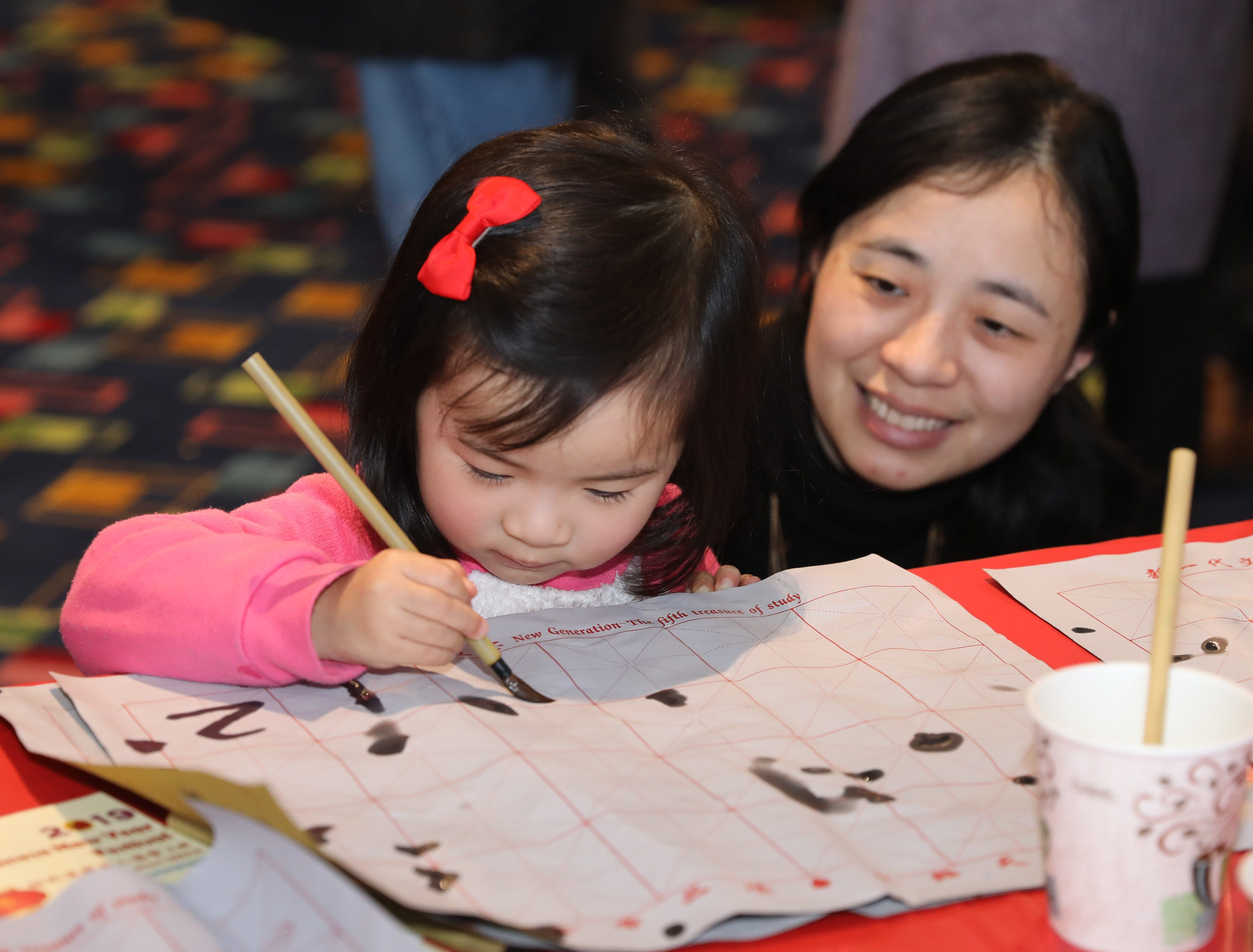 Jie Gao looks on as her daughter Kate Xin, 2, writes some numbers on a grid, during the 30th Chinese New Year Festival, the Year of the Pig, sponsored by WACA (Westchester Association of Chinese Americans), at The Performing Arts Center at Purchase College SUNY, Feb. 9, 2019.