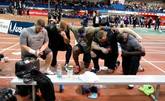 Shot putters pray after Kemoy Campbell of Jamaica collapsed while running in the men's 3000 meter race during the 2019 Millrose Games at the New Balance Armory in Manhattan Feb. 9, 2019. Campbell was carried from the track on a stretcher.