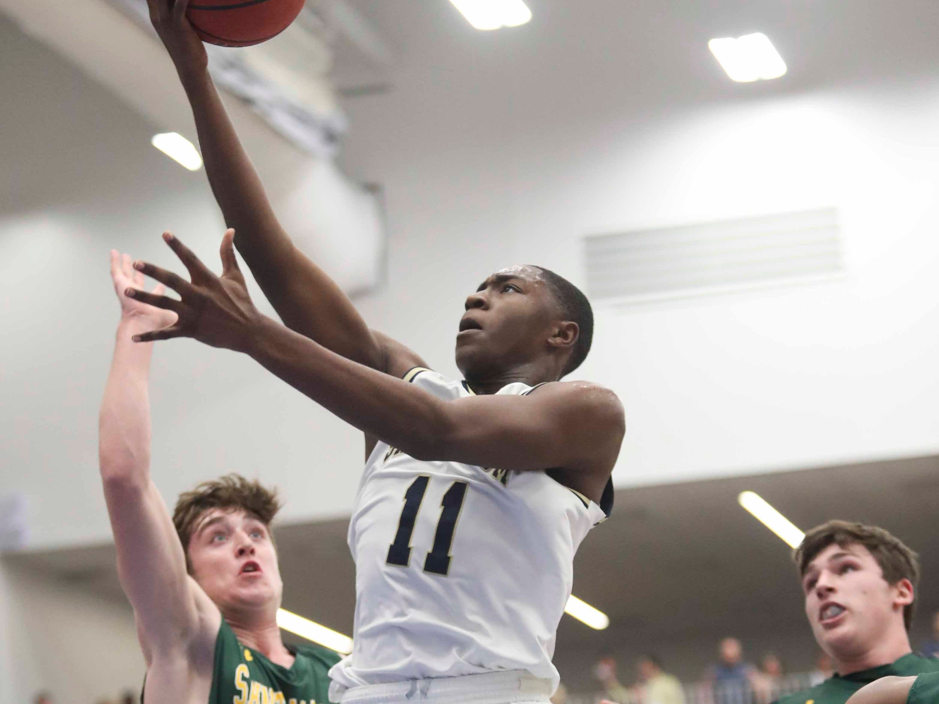 Salesianum's Darnell Vaughn (11) goes to the basket against St. Mark's Victor Marcelo (left) and Eric Ludman in the SL24 Memorial Basketball Classic at the 76ers Fieldhouse in Wilmington Friday.