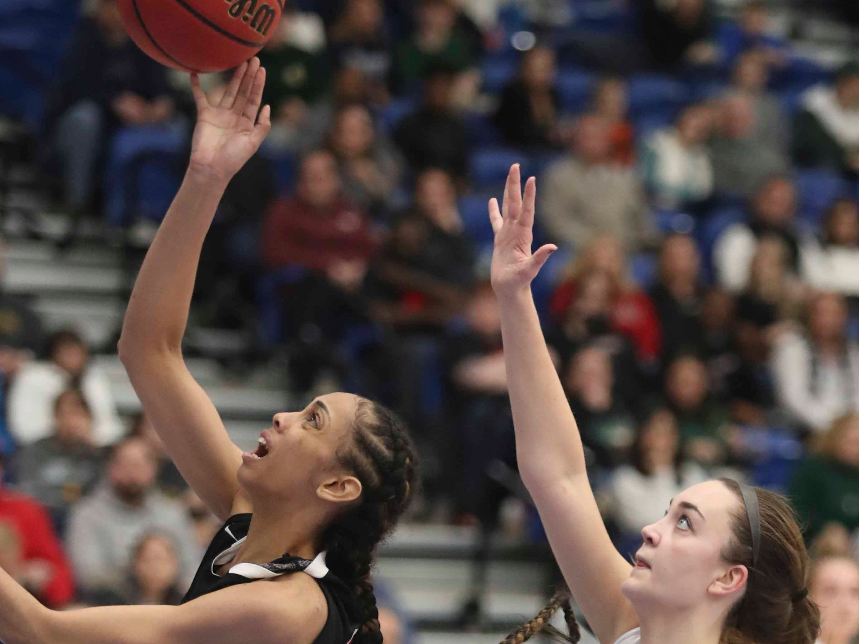 Ursuline's Kaleigh White (left) scores ahead of St. Mark's Kayla Wolff in the SL24 Memorial Basketball Classic at the 76ers Fieldhouse in Wilmington Friday.