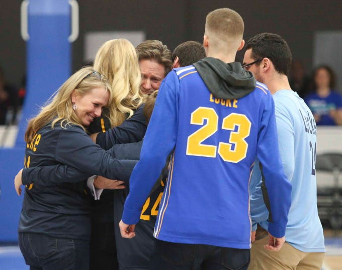 Sean Locke's family gathers at midcourt after ceremonies between games in the SL24 Memorial Basketball Classic at the 76ers Fieldhouse in Wilmington Friday.