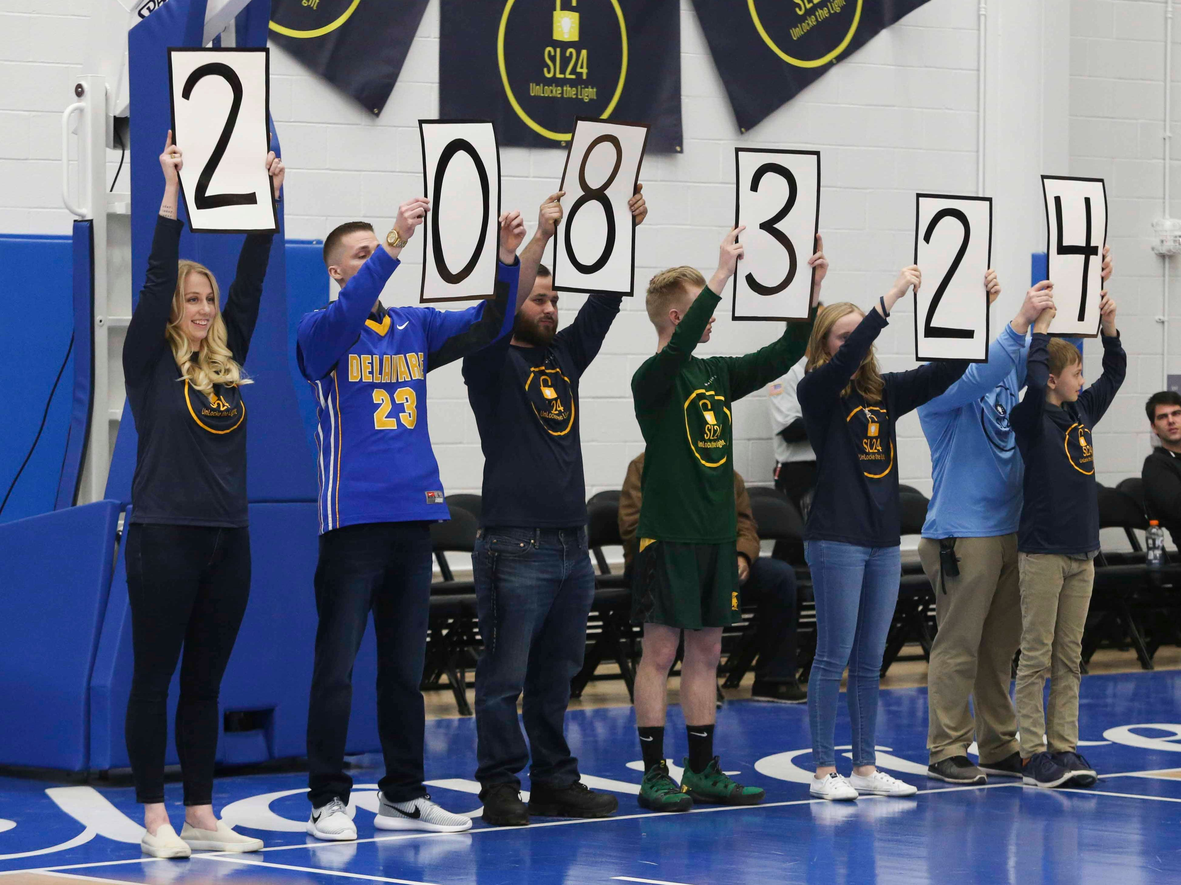 Siblings of Sean Locke signal the amount of money raised for the Unlocke the Light Foundation - $208,324 - at  the SL24 Memorial Basketball Classic held in his memory at the 76ers Fieldhouse in Wilmington Friday.