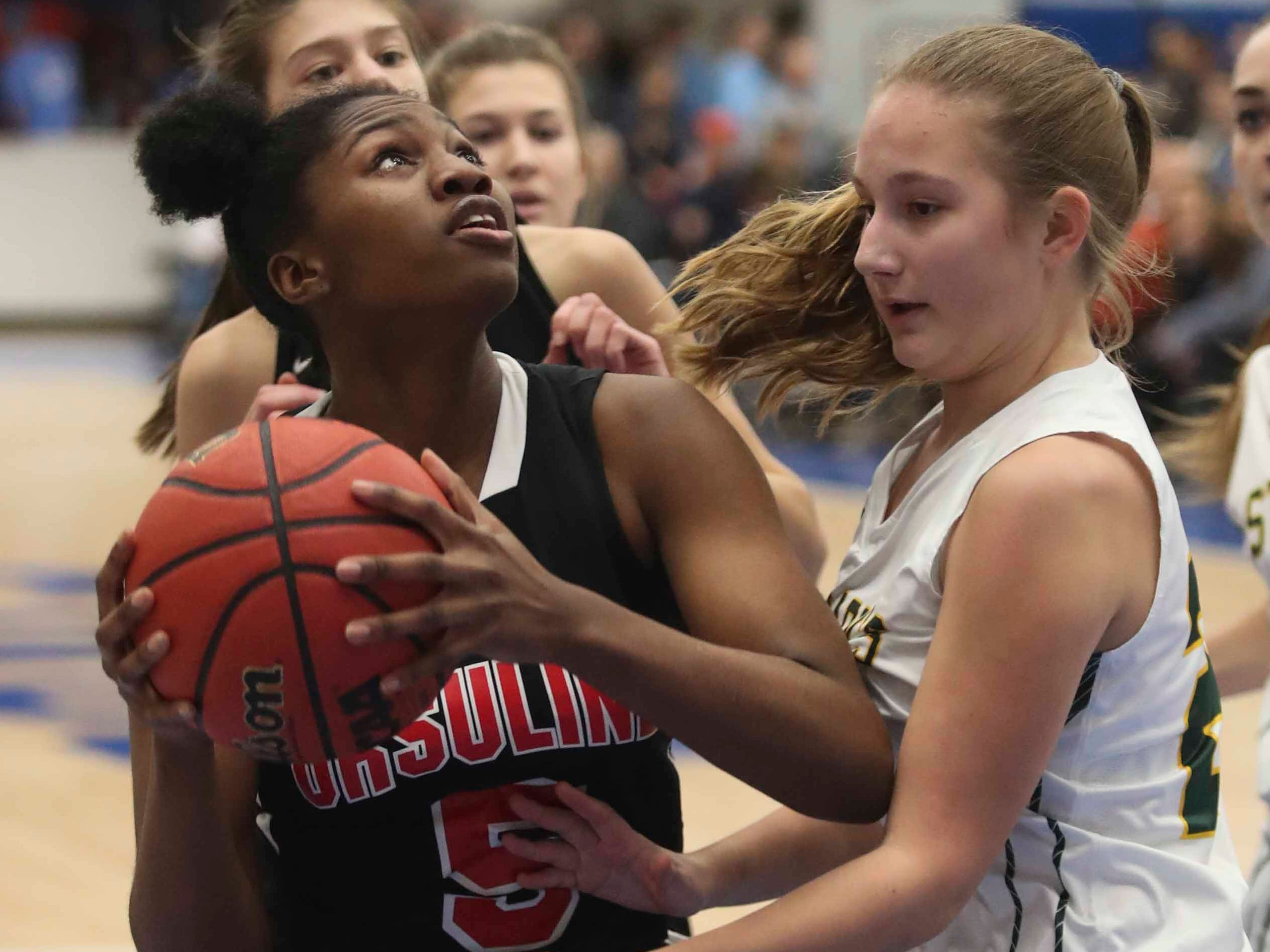 Ursuline's Kay Wulah (left) goes to shoot in front of St. Mark's Madalyn Lenick in the SL24 Memorial Basketball Classic at the 76ers Fieldhouse in Wilmington Friday.