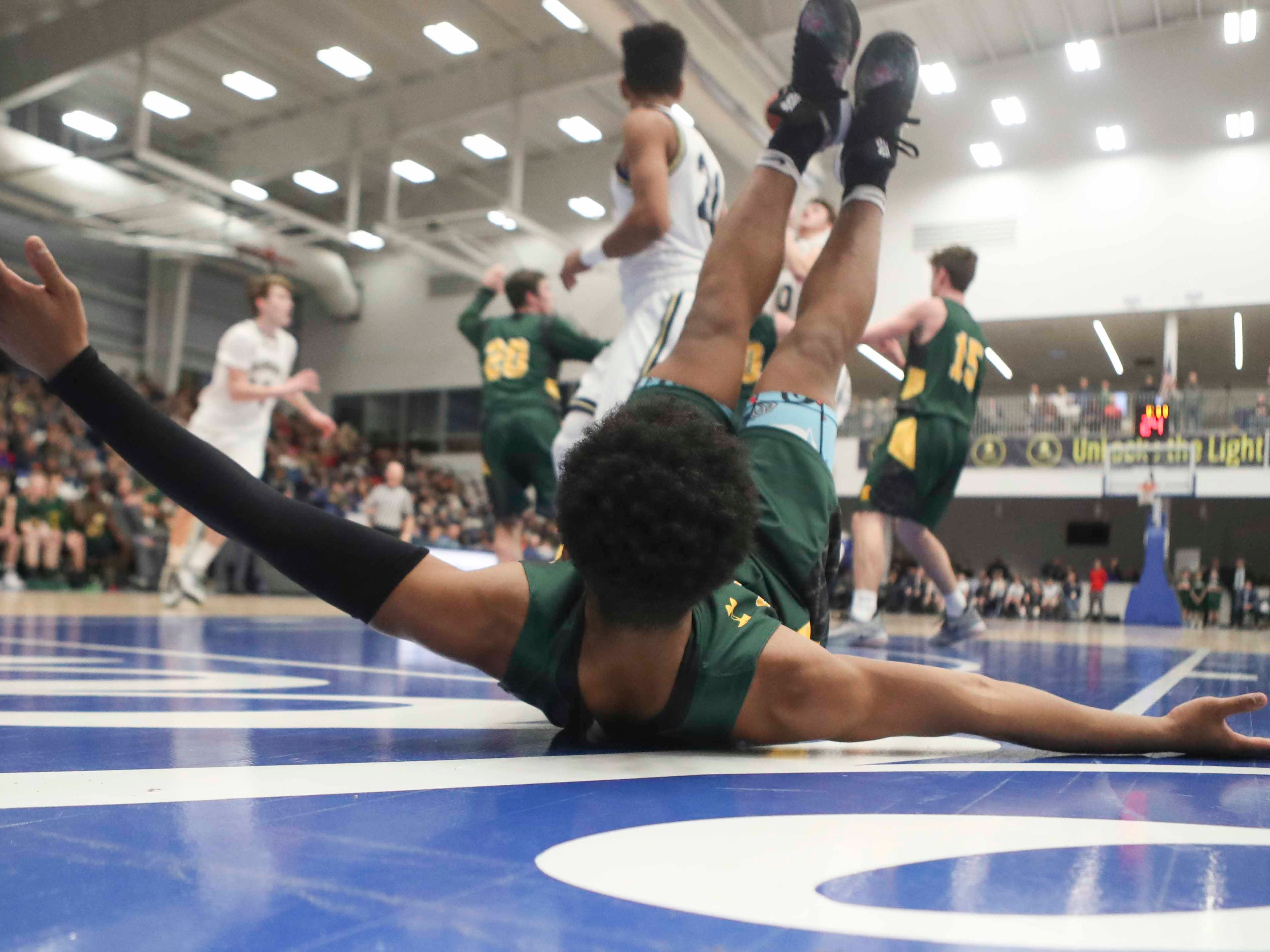 St. Mark's Blaec Sanders is sent sprawling under the basket against Salesianum in the SL24 Memorial Basketball Classic at the 76ers Fieldhouse in Wilmington Friday.