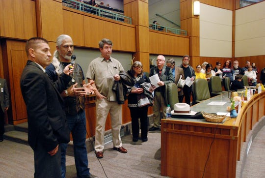 In this Monday, Feb. 4, 2019, photo, Rico Giron, second from left, of Las Vegas, N.M., and a line of New Mexico residents, voice disapproval of a state bill that would temporarily restrict firearms access for people considered to be at risk to themselves or others, at a legislative committee hearing in Santa Fe, N.M. States have seen a surge of interest in laws intended to make it easier to disarm people who show signs of being violent or suicidal, since last year's mass shooting at a Florida high school. (AP Photo/Morgan Lee)