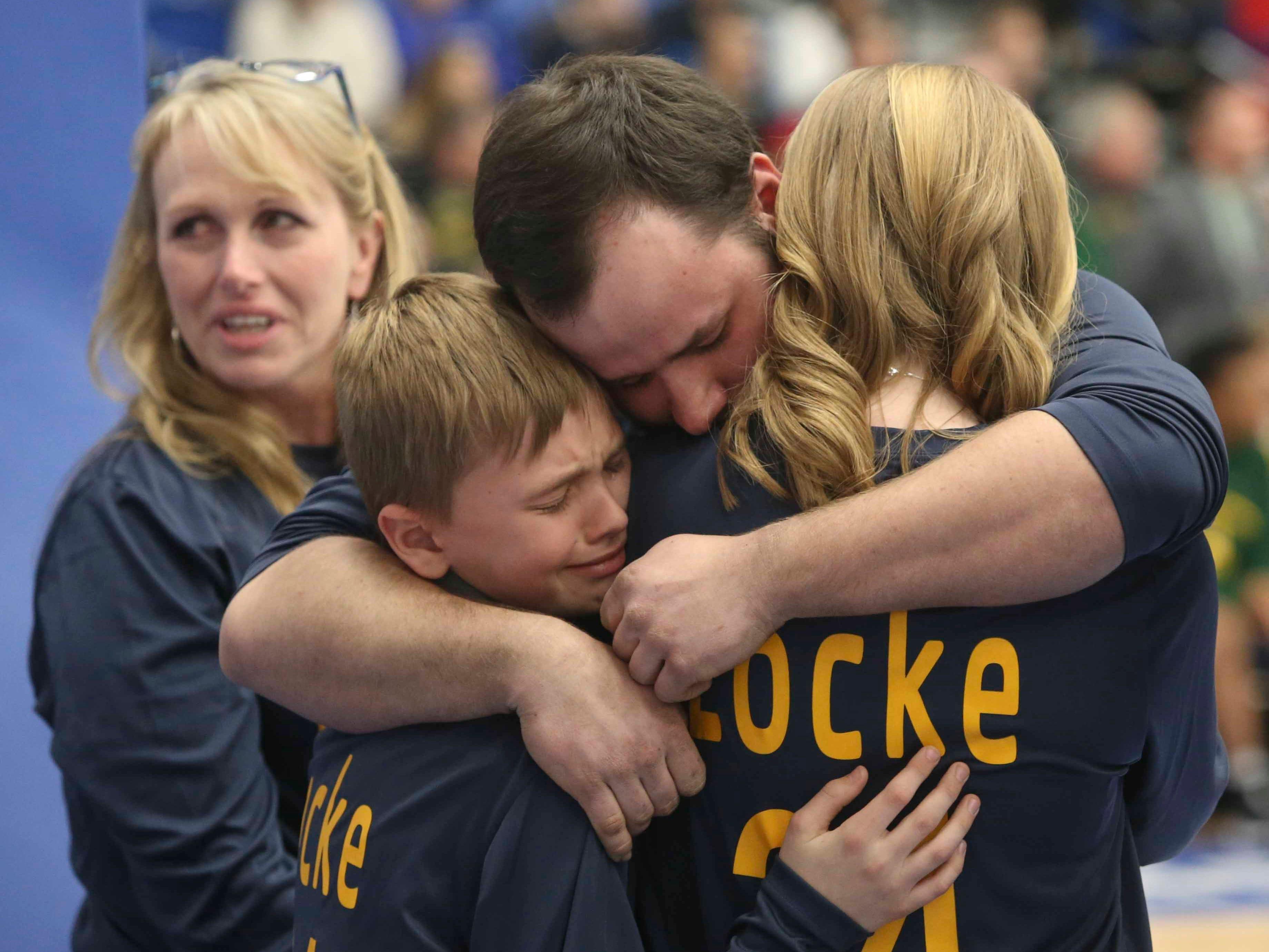 Siblings of Sean Locke hug during ceremonies between games in the SL24 Memorial Basketball Classic at the 76ers Fieldhouse in Wilmington Friday.