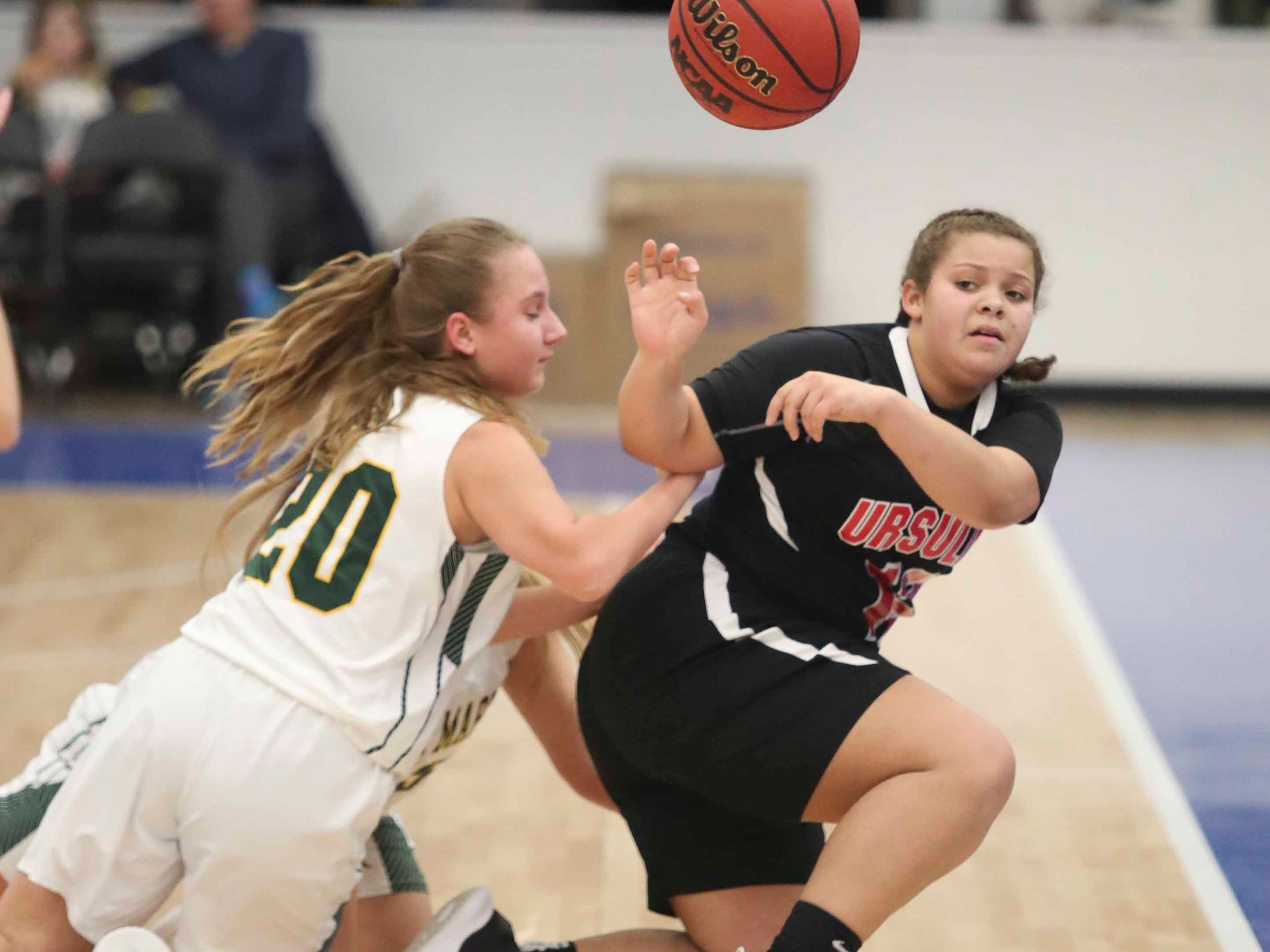 St. Mark's Madelyn Lenick (left) converges with a teammate on Ursuline's Taelynn Brooks in the SL24 Memorial Basketball Classic at the 76ers Fieldhouse in Wilmington Friday.