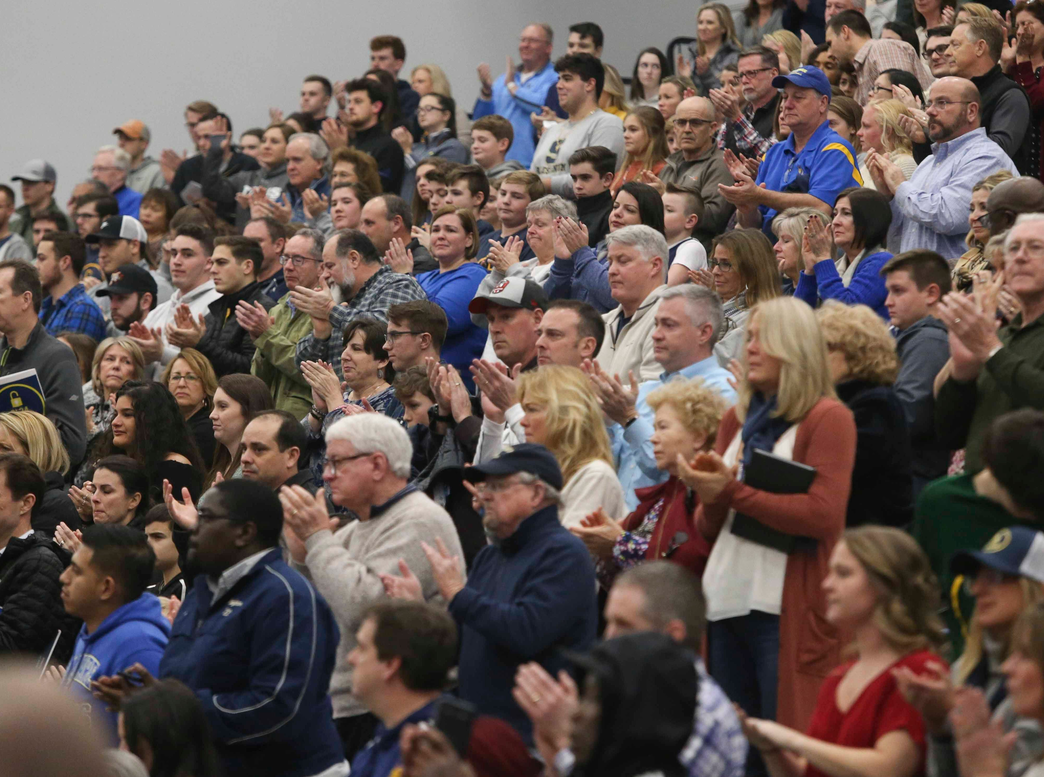 Attendees applaud the Locke family in ceremonies between games in the SL24 Memorial Basketball Classic at the 76ers Fieldhouse in Wilmington Friday.