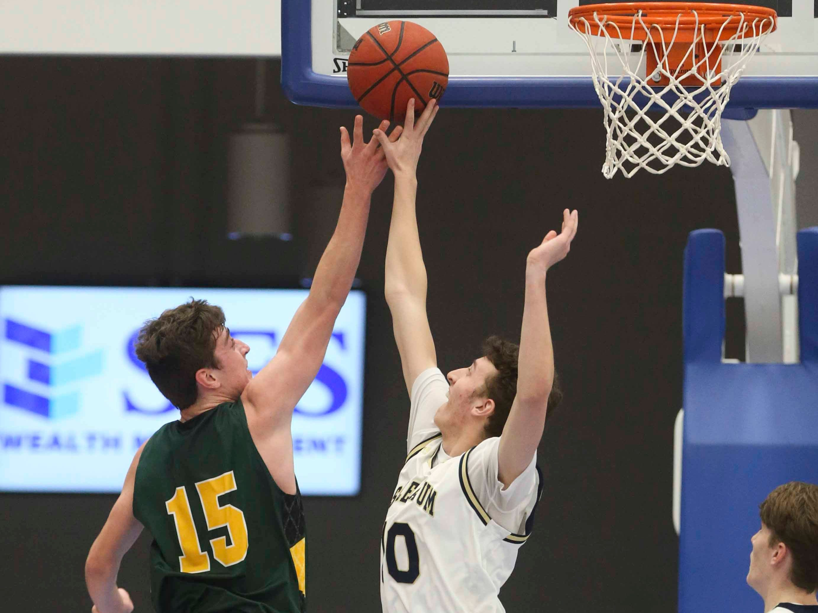 Salesianum's Jack Brown (right) stretches to get a piece of the ball against St. Mark's Victor Marcelo in the SL24 Memorial Basketball Classic at the 76ers Fieldhouse in Wilmington Friday.