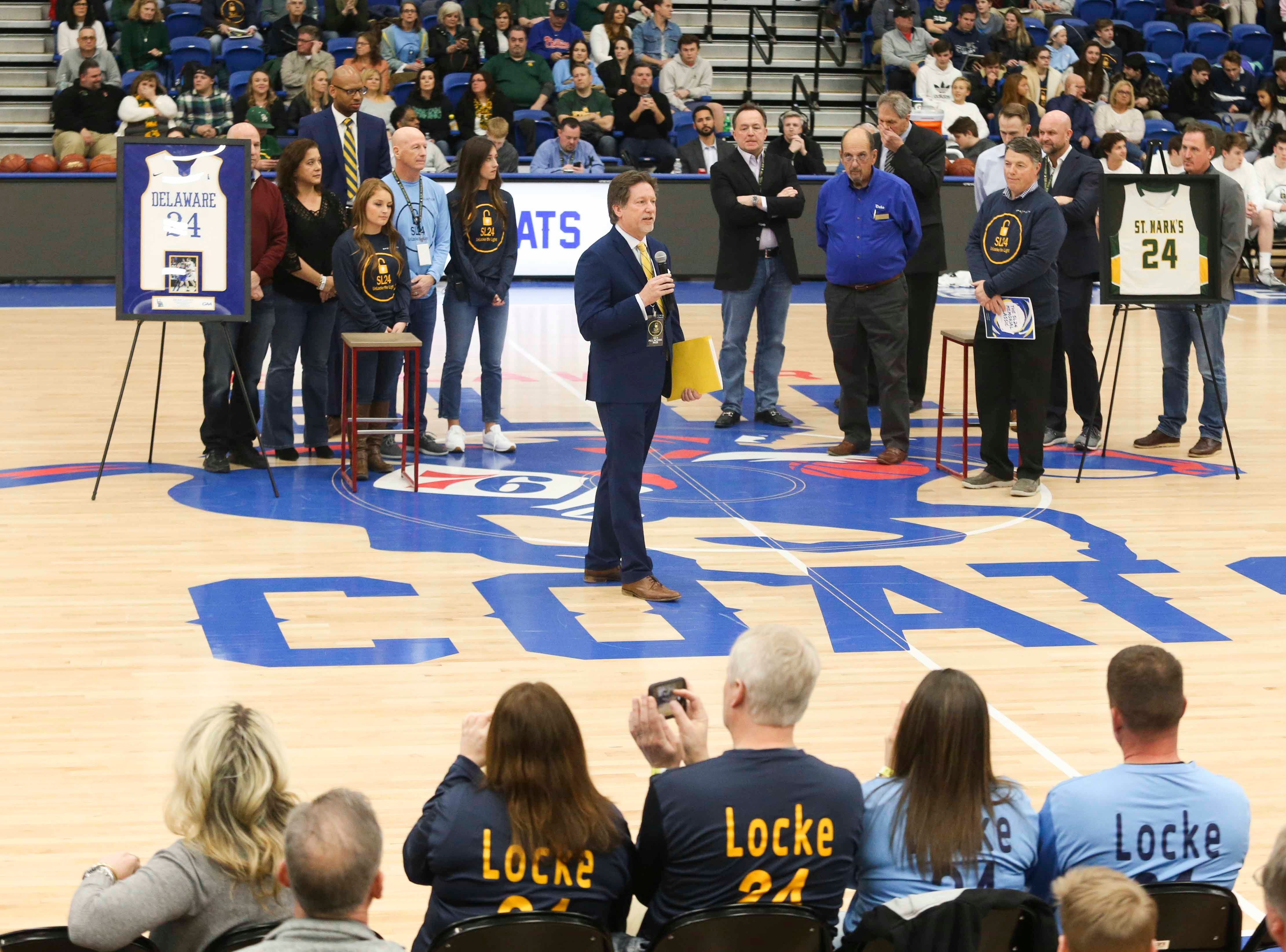 Chris Locke, father of Sean Locke, joins other supporters of the Unlocke the Light Foundation between games in the SL24 Memorial Basketball Classic at the 76ers Fieldhouse in Wilmington Friday.