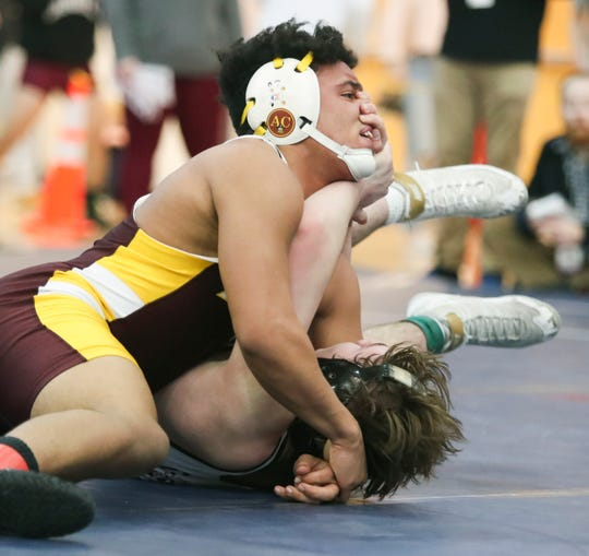 Milford's Rafael Mejia (top) works toward a win at 170 pounds against Caravel's Anthony Bernieri in the DIAA dual meet championships Saturday at Smyrna High School.